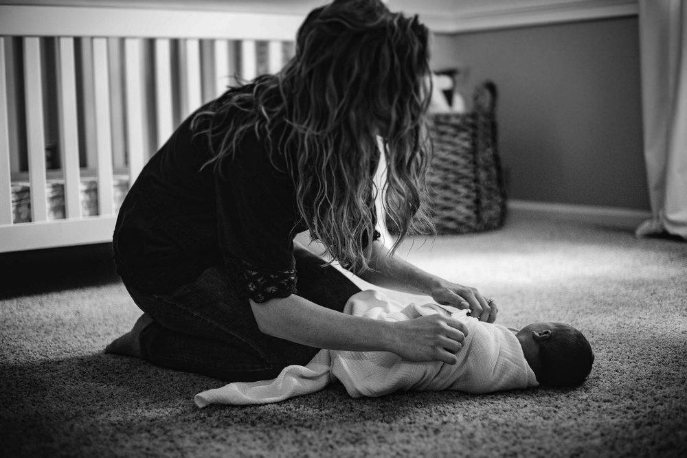 Mom swaddles newborn on floor from Huntsville and Madison Alabama lifestyle newborn photographer Rachel K Photo