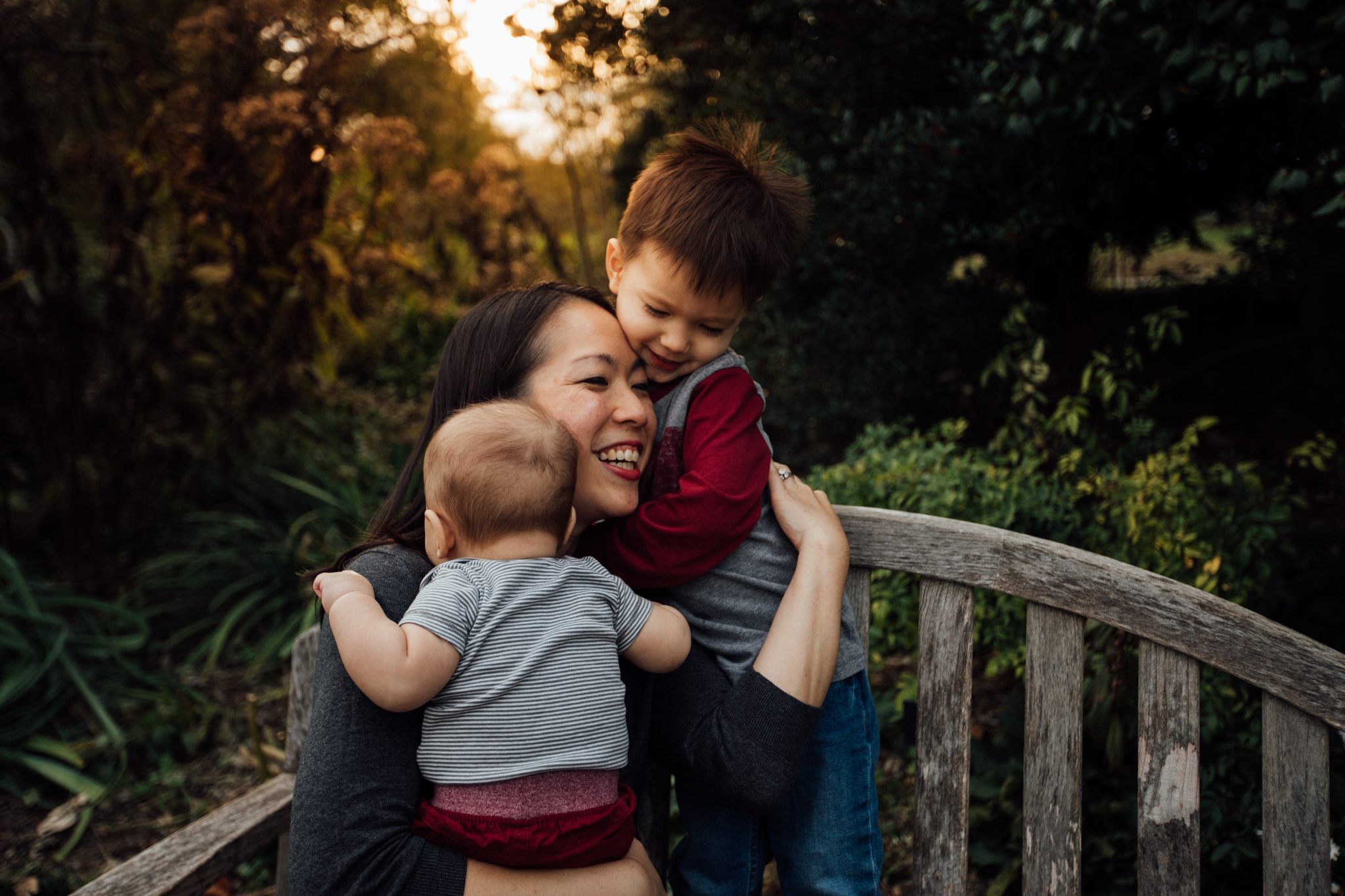 Momma smiles holding two sons on bench by Madison and Huntsville Alabama family photographer Rachel K Photo