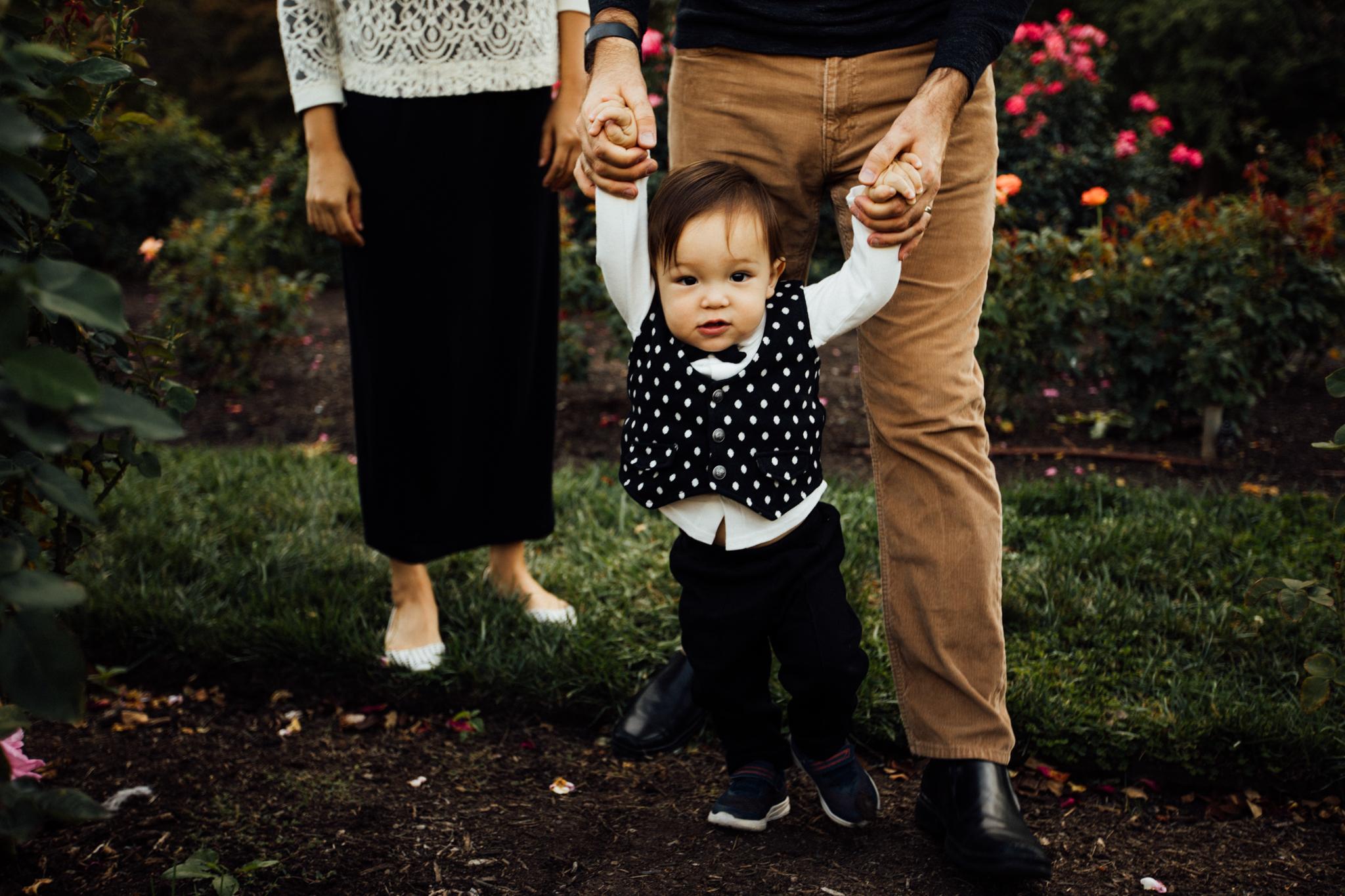 Toddler walks holding dad's hands Madison and Huntsville Alabama family photographer Rachel K Photo