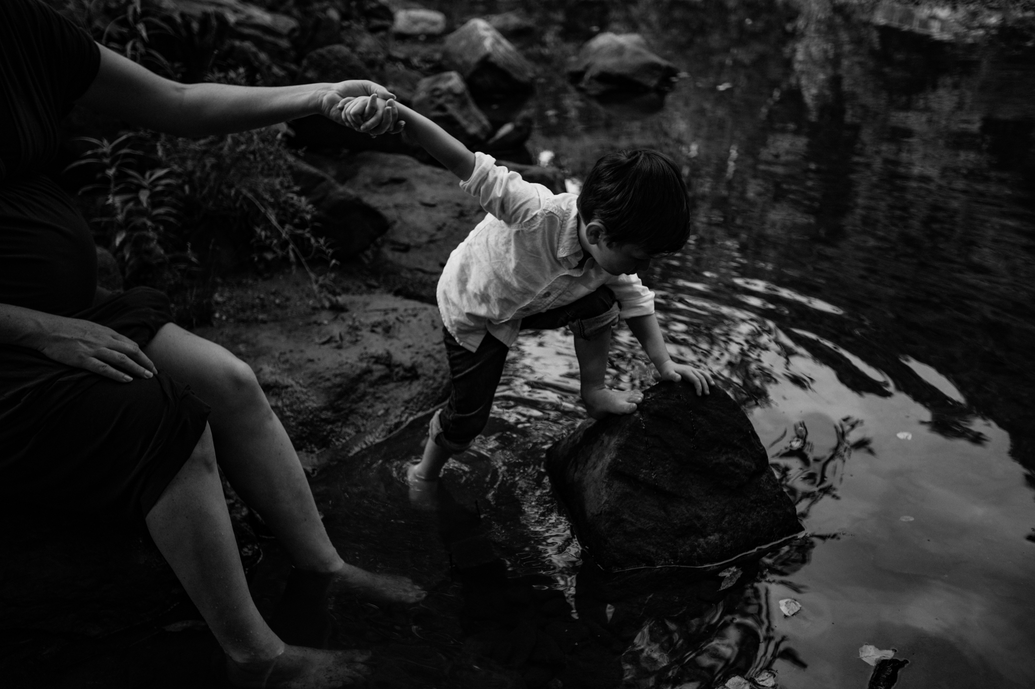 Mother holds son's hand as he plays in creek by Madison and Huntsville Alabama family photographer Rachel K Photo