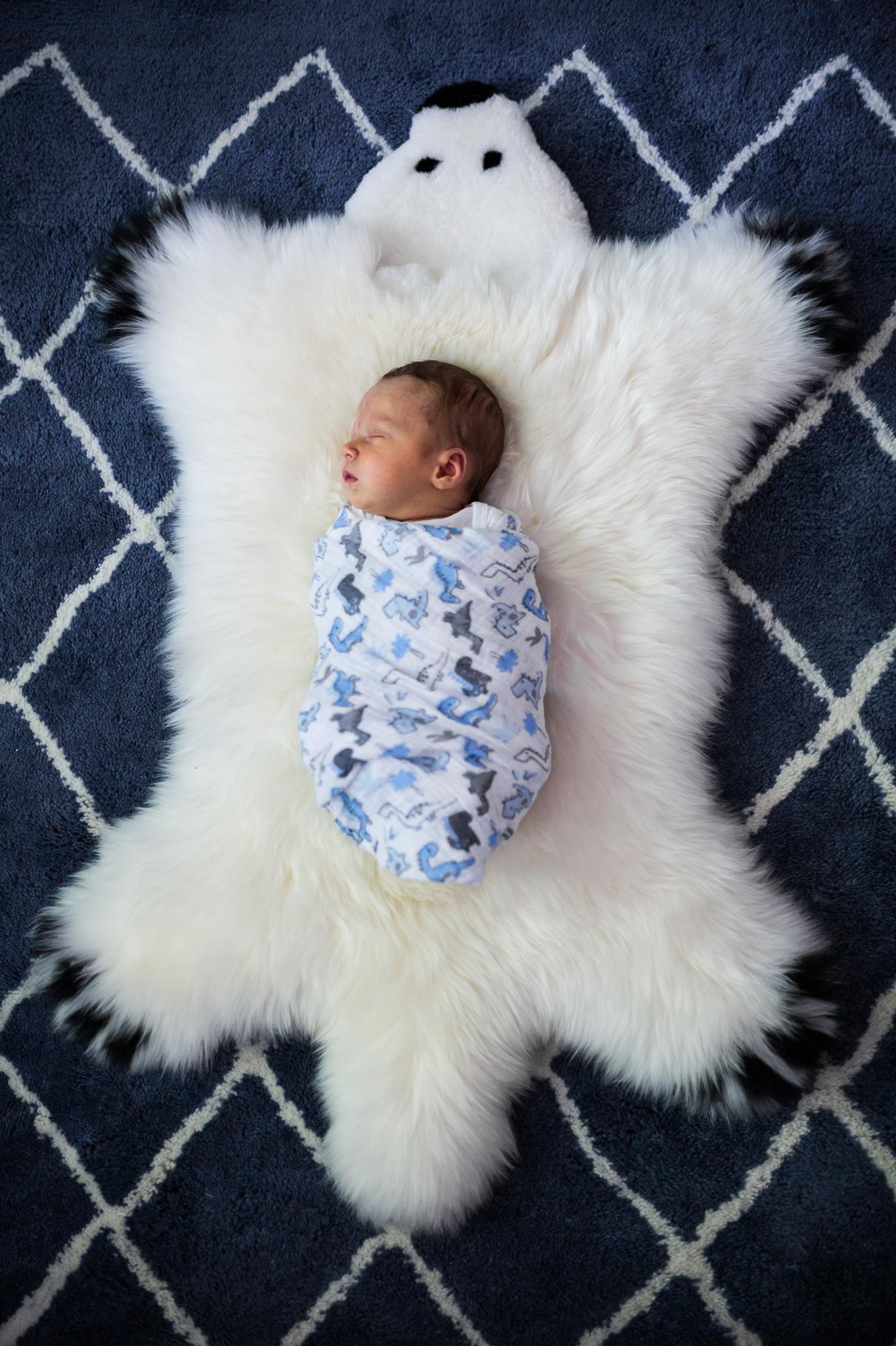 Swaddled baby lays on bear blanket from Huntsville and Madison Alabama lifestyle newborn photographer Rachel K Photo