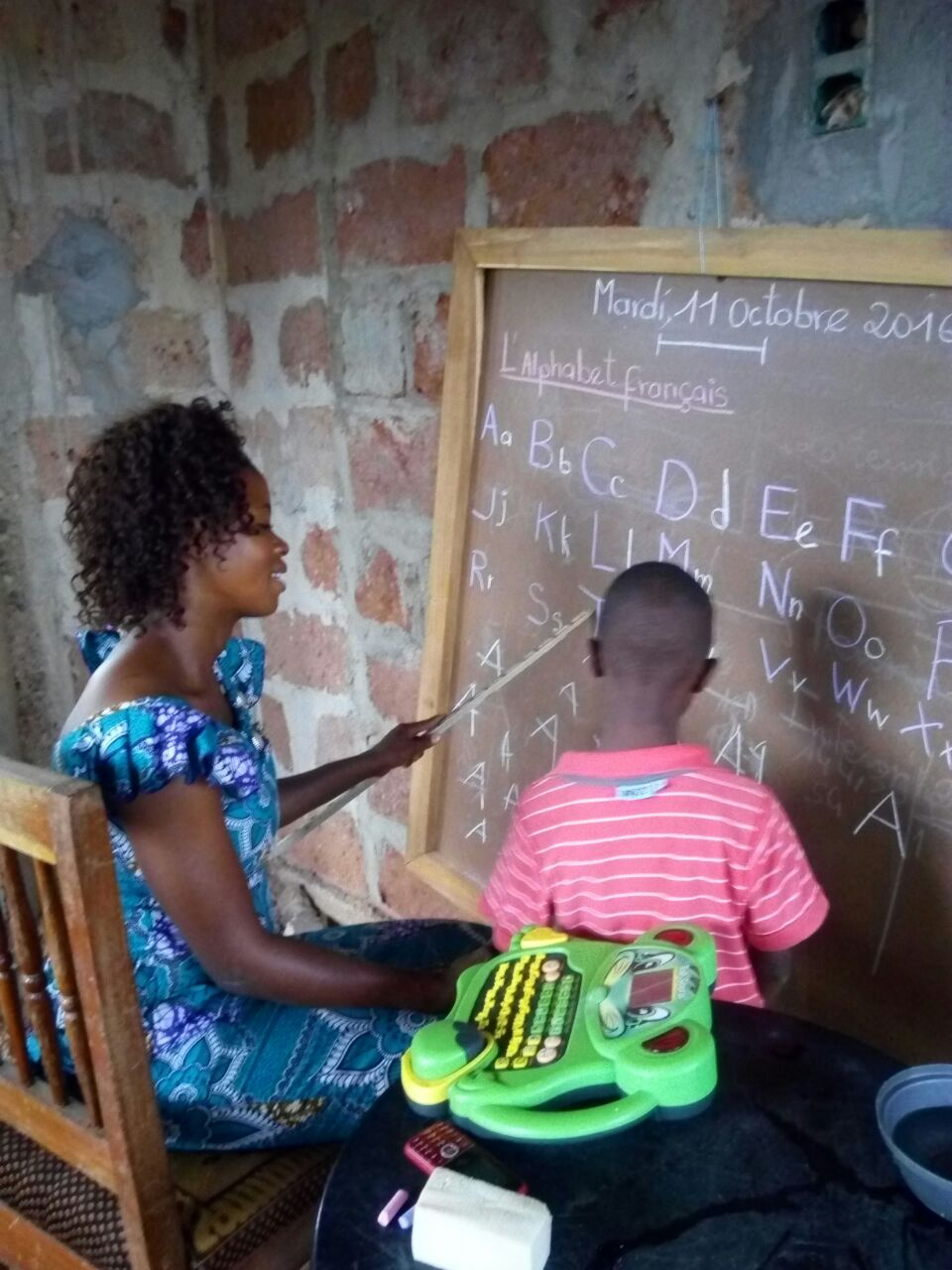 Mme Ogbon teaches Sele the alphabet. Sele has special needs and was formerly asked to leave school due to lack of resources. We're happy to report that he is now in the 1st grade after being in our program last year.