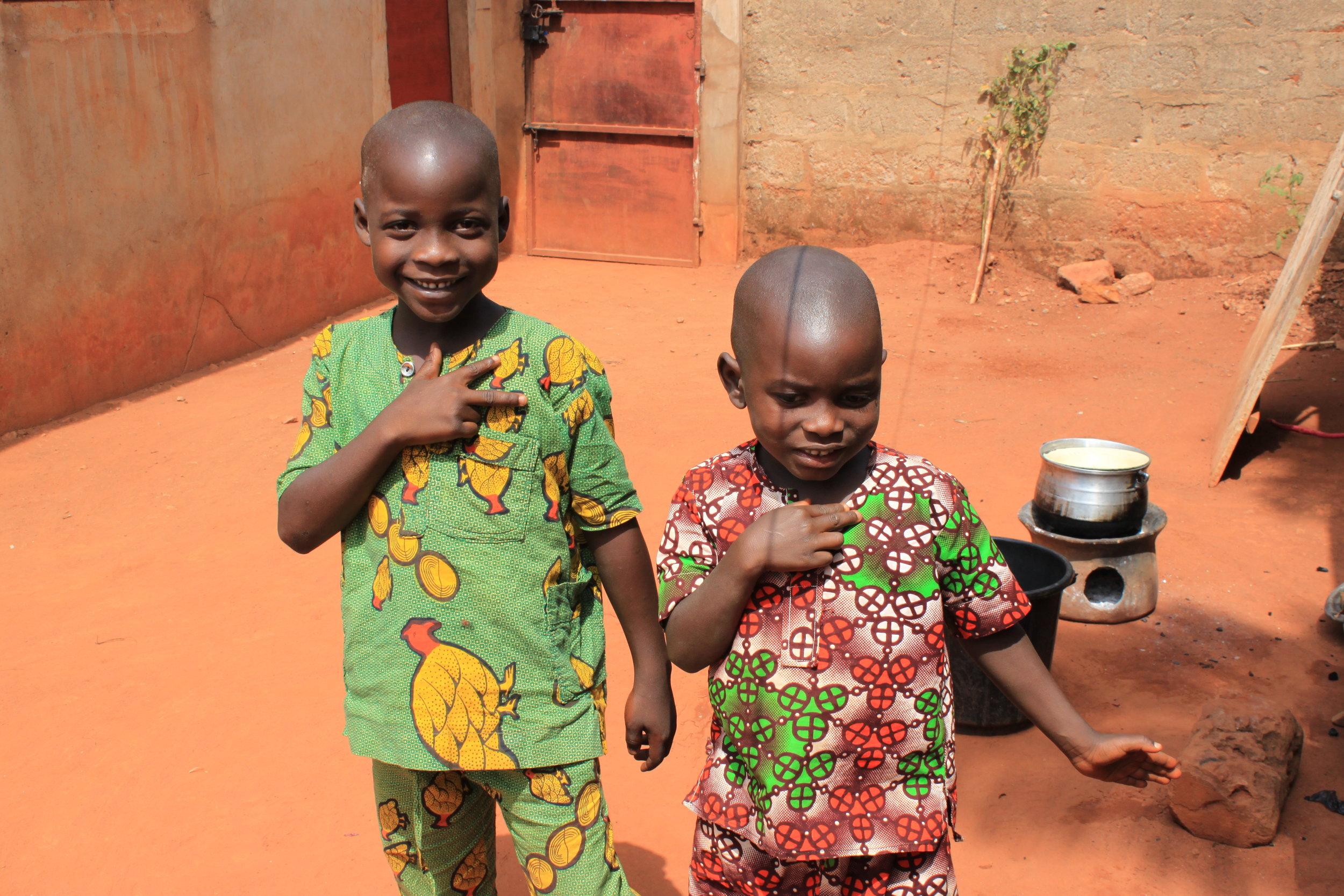 "Audrey's brothers hanging out in their courtyard in Abomey, Benin doing the ""Superman"" pose that was so popular earlier this year."