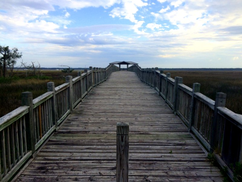 A wooden walkway stretching out over a marsh in St. Marys, Georgia.