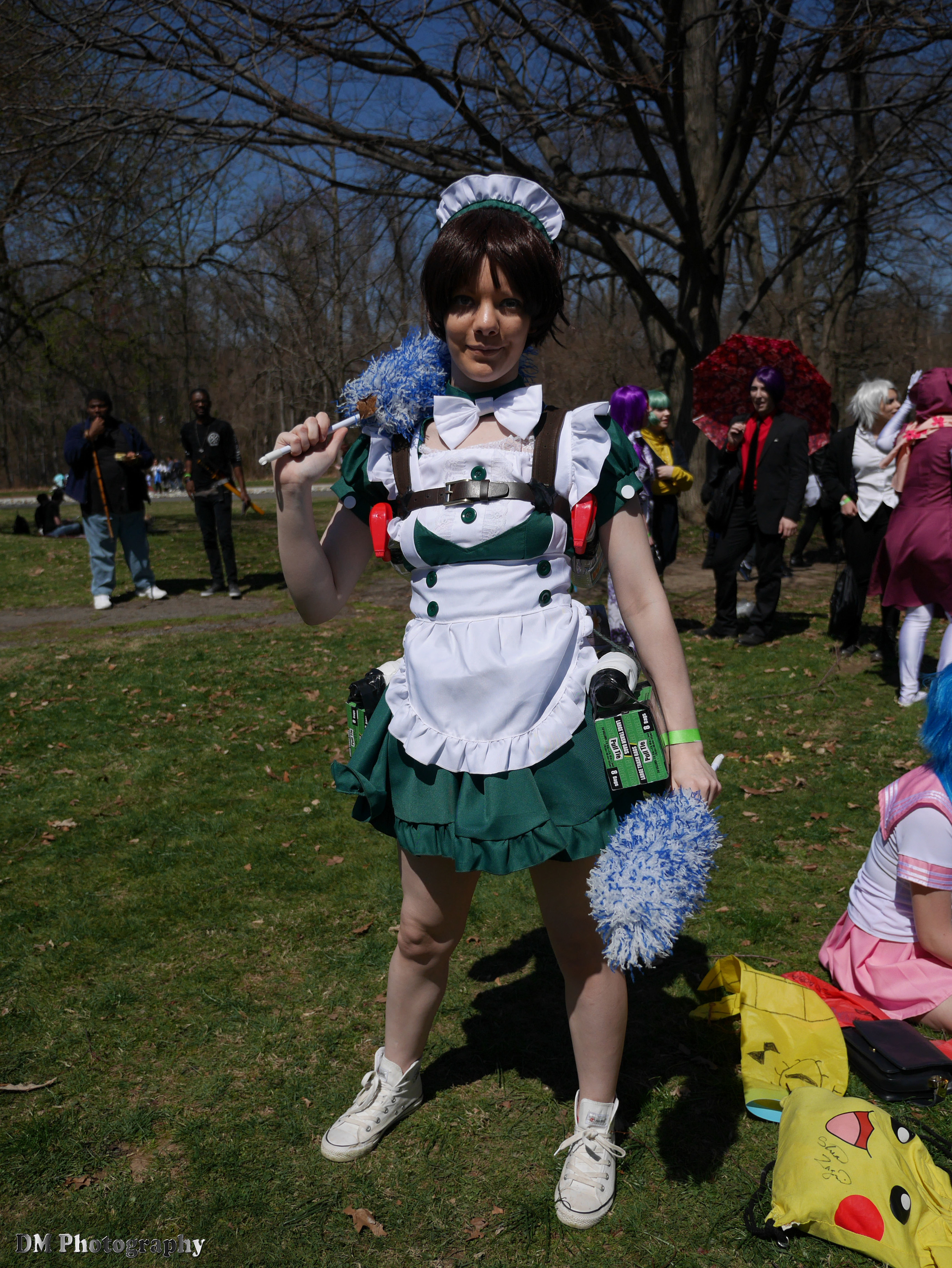 An original genderbend cosplay design of Eren Yaeger from Attack on Titan featuring Eren in a maid outfit with all of his weapons and gear replaced by cleaning products