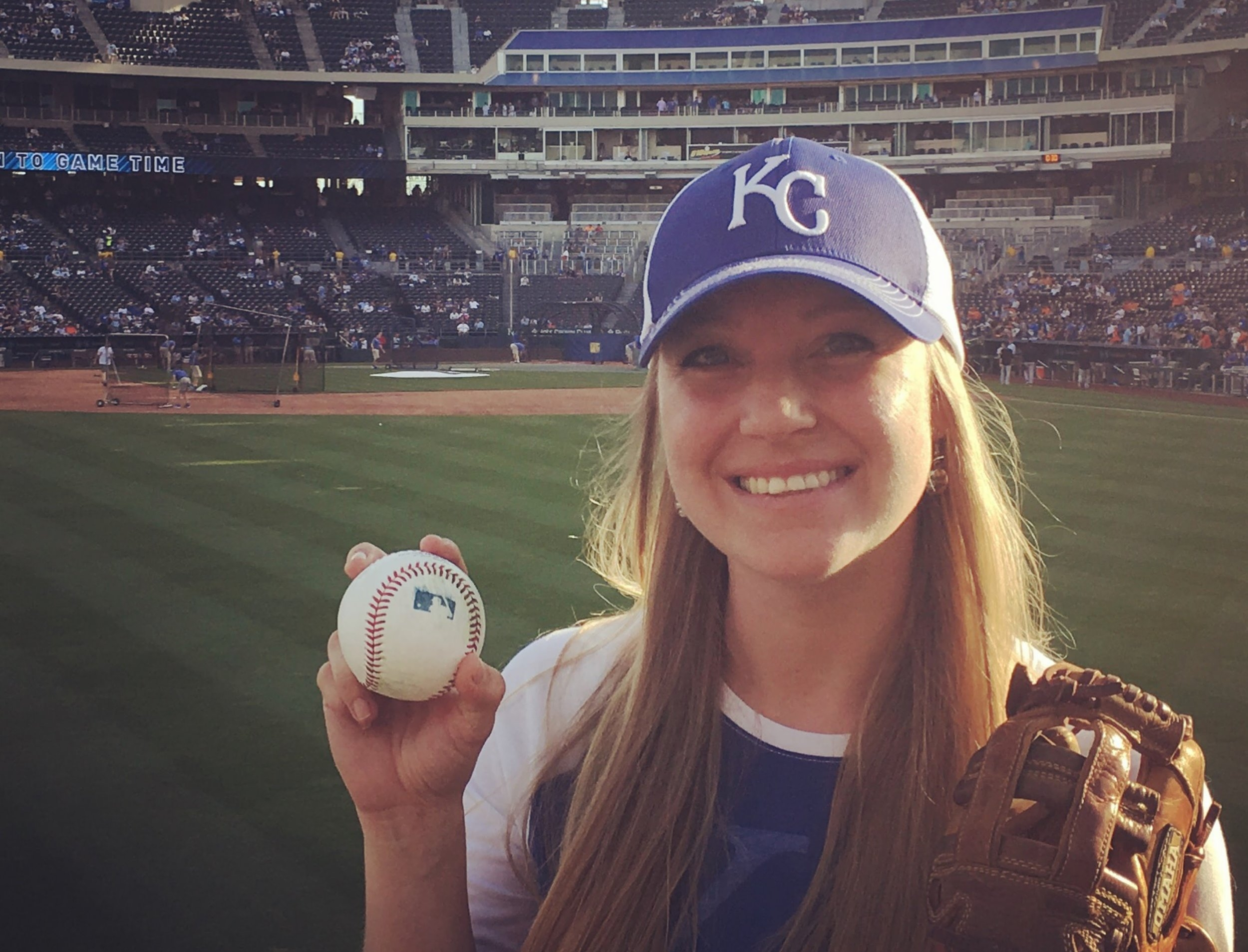 Blair is displaying one of the many batting practice ball she's caught.