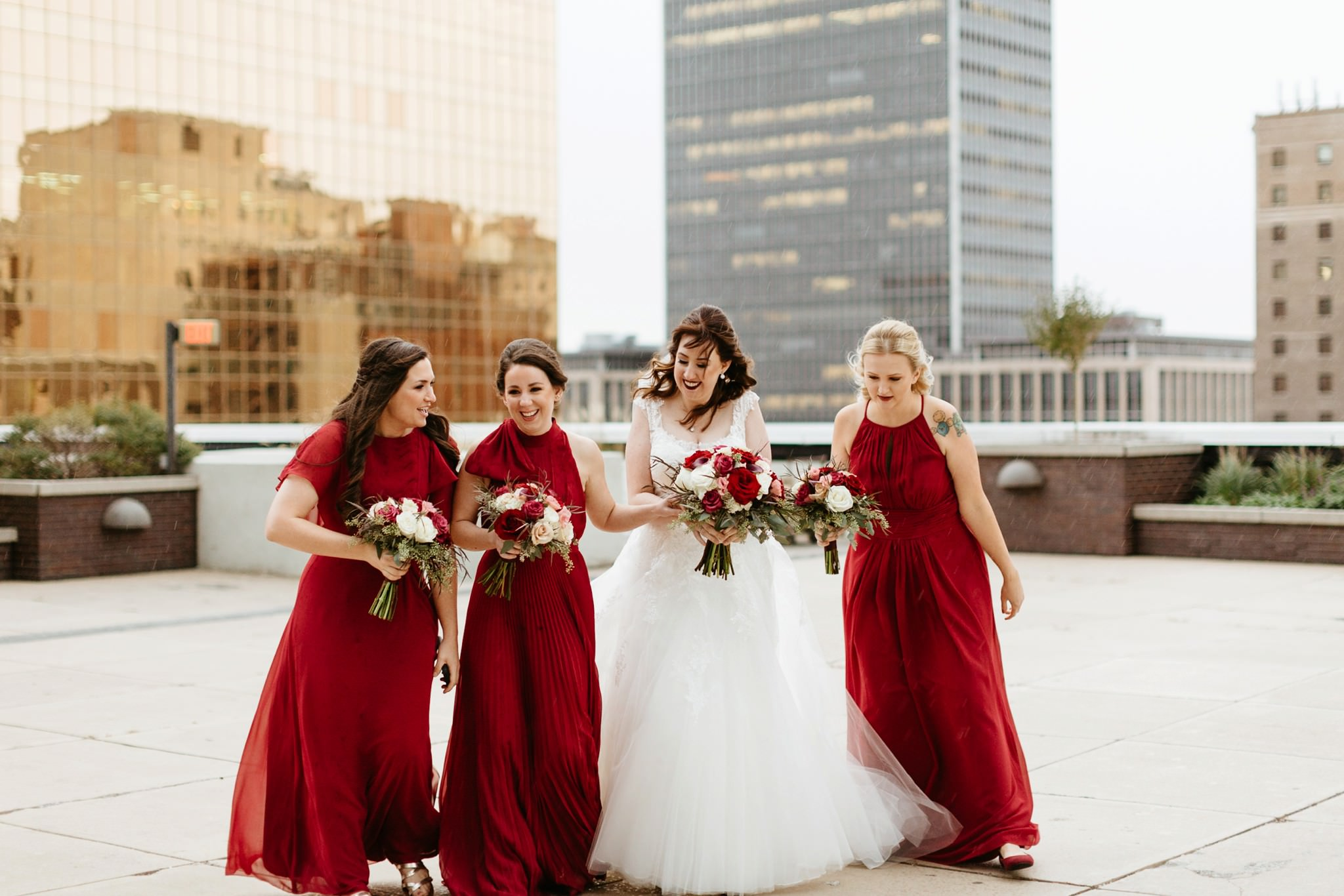 bride-and-bridesmaids-laugh-during-wedding-portraits-at-the-regions-tower-rooftop