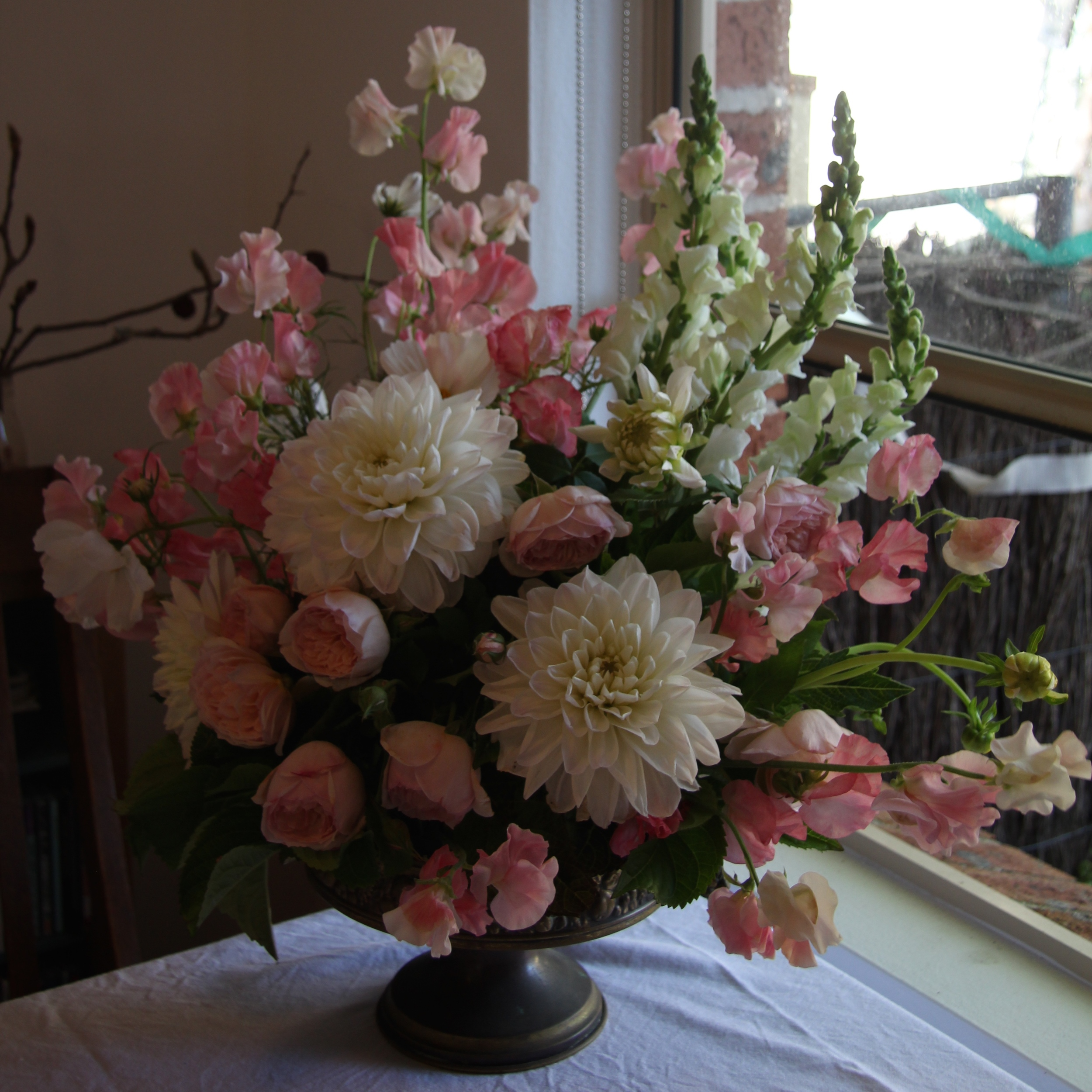 pink white floral arrangement in brass urn