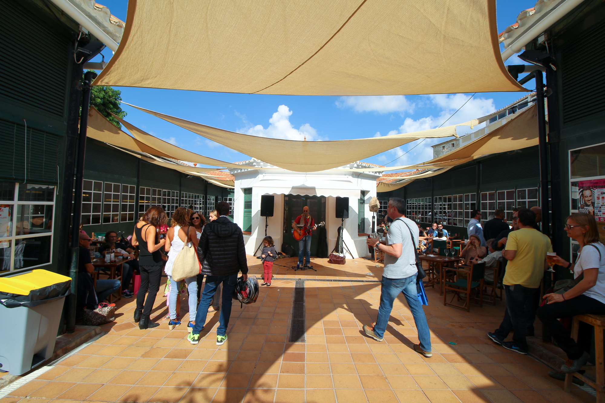 You enter into a large open area (atrium?). As you can see there's a man with a guitar, tables all around the side with merry people, and you can enter the surrounding building on either side to grab tapas and drinks.