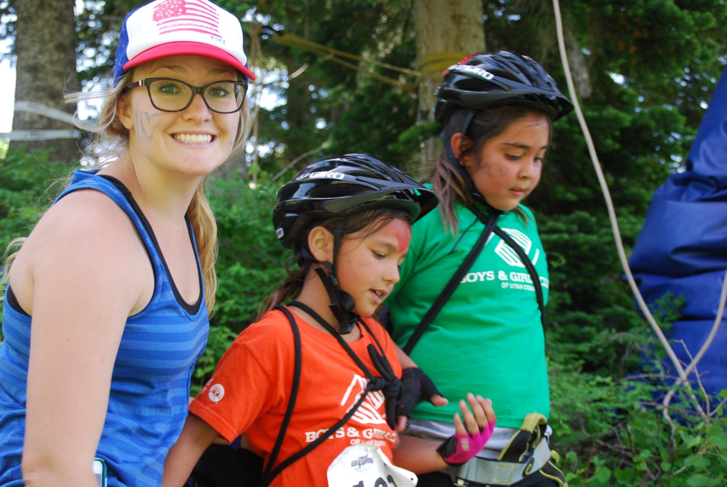Fellow, Macie Bayer, helping two kids get onto the zipline