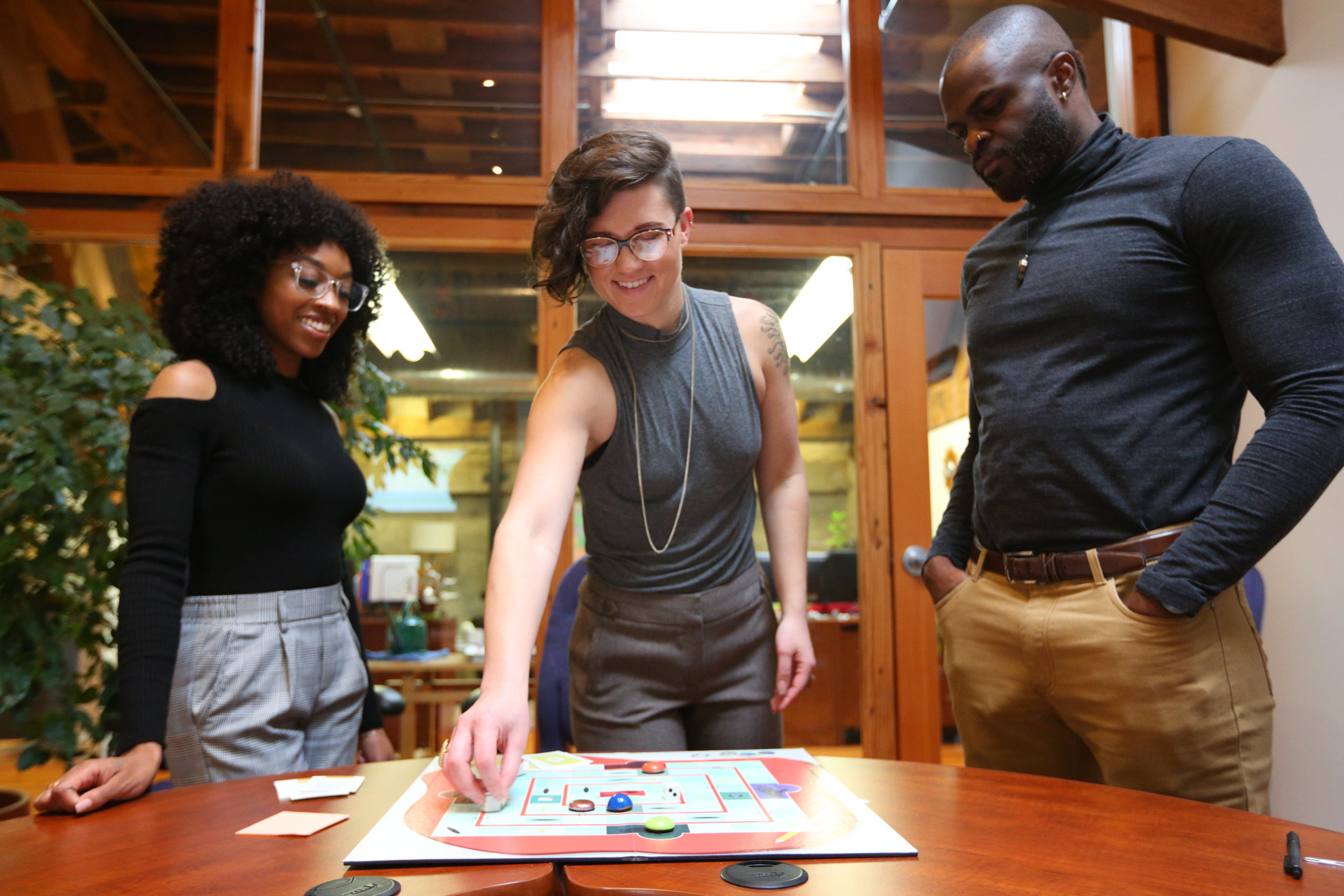 Fellows playing a cooperative board game that is designed to simulate common experiences and barriers faced upon entering the social sector.