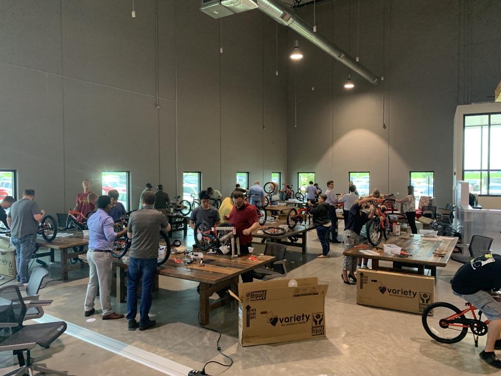 Volunteers from HyVee building bikes.