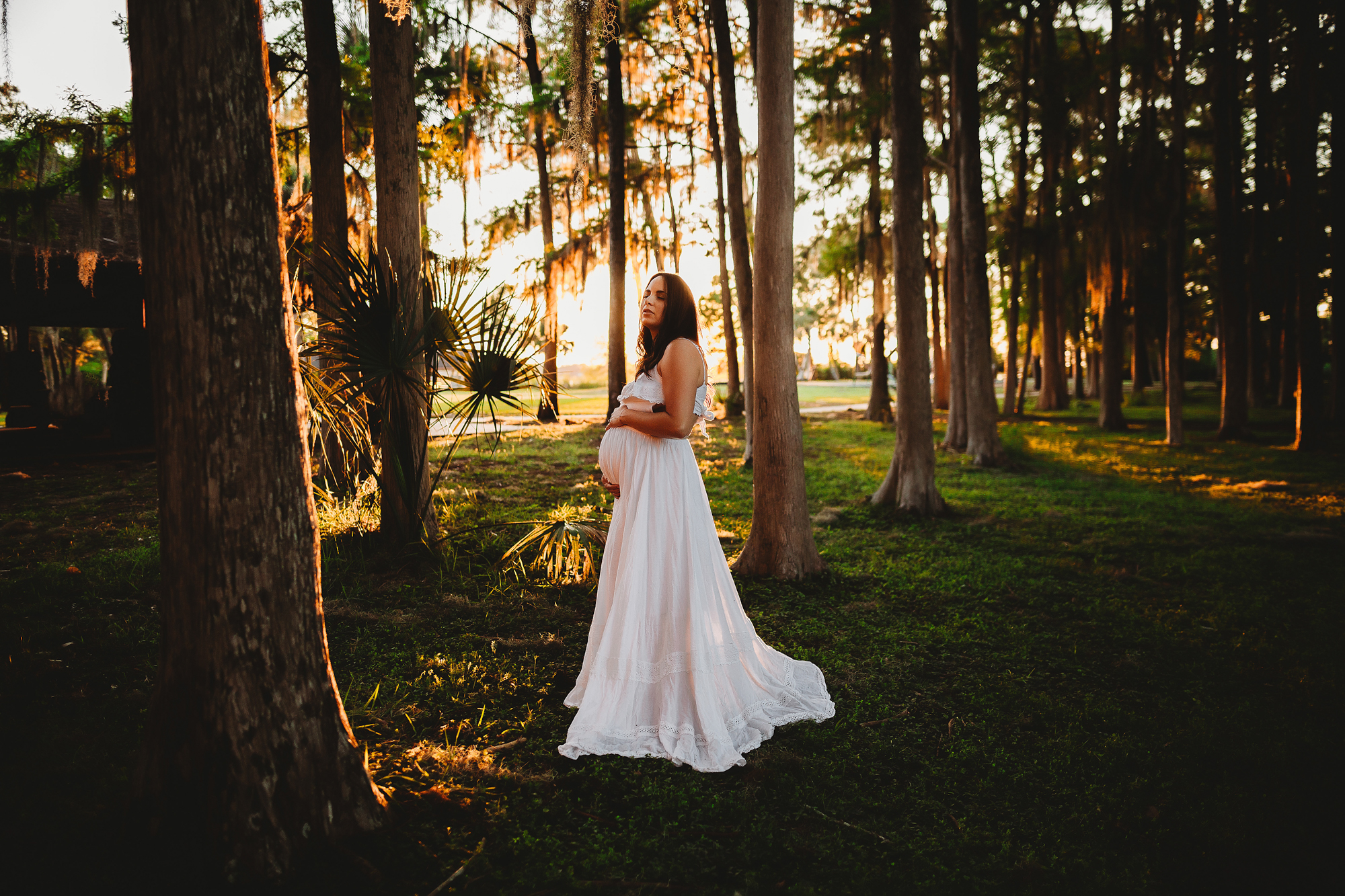 enchanting maternity portraits in the forest at sundown. John chestnut sr park maternity photo shoot in white dress with sunshine glowing through the trees