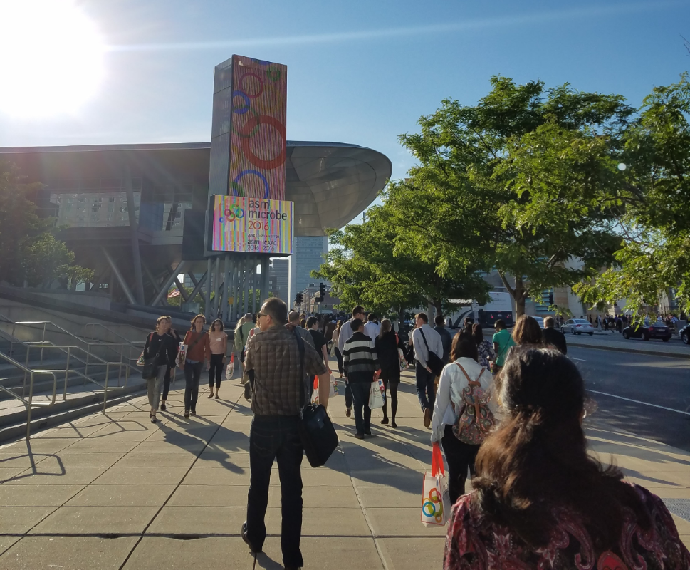 A sunny day outside the convention center. In a near-future dystopia, convention attendees could be tracked across the city by searching surveillance feeds for their distinctive swag bags.