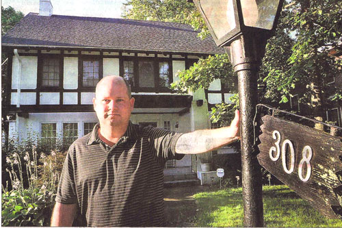 Patrick Beckel stands in front of the house he nearly had stolen from him by a con man, who essentially tricked him into thinking he had sold it to the man. Staff photo by Bill Lackey.