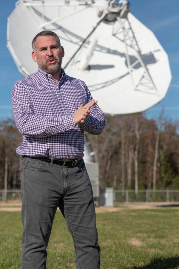 Josh Brooks stands in front of Antenna 8 at the Blossom Point Tracking Facility. NRL Photo by Emanuel Cavallaro.