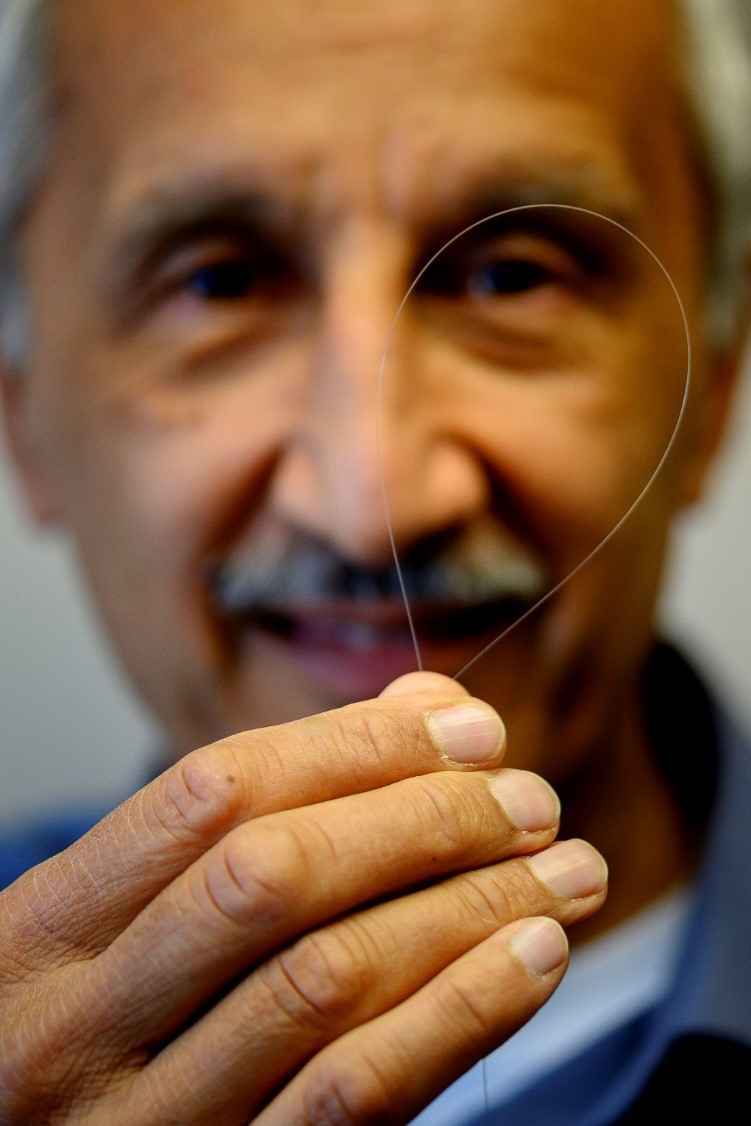 Jas Sanghera, U.S. Naval Research Laboratory branch head for Optical Materials and Devices, holds up optical fiber that will be used to produce eye safer lasers at U.S. NRL, DC on March 26, 2019. (U.S. Navy photo by Jonathan Steffen)