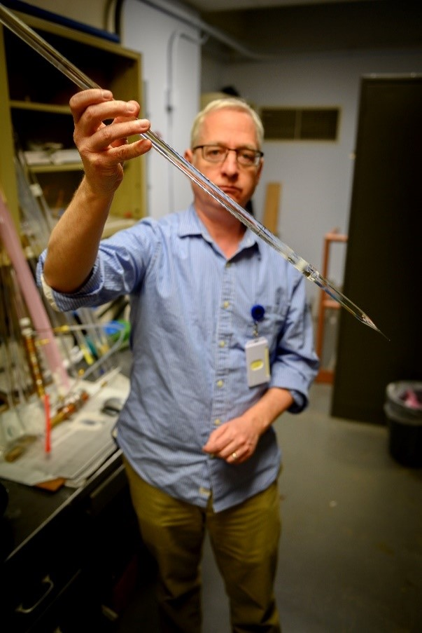 Colin Baker, U.S. Naval Research Laboratory, holds a silica glass rod (optical preform) that will be pulled into an optical fiber suitable for production of an eye safer laser at U.S. NRL, DC on March 26, 2019. (U.S. Navy photo by Jonathan Steffen)