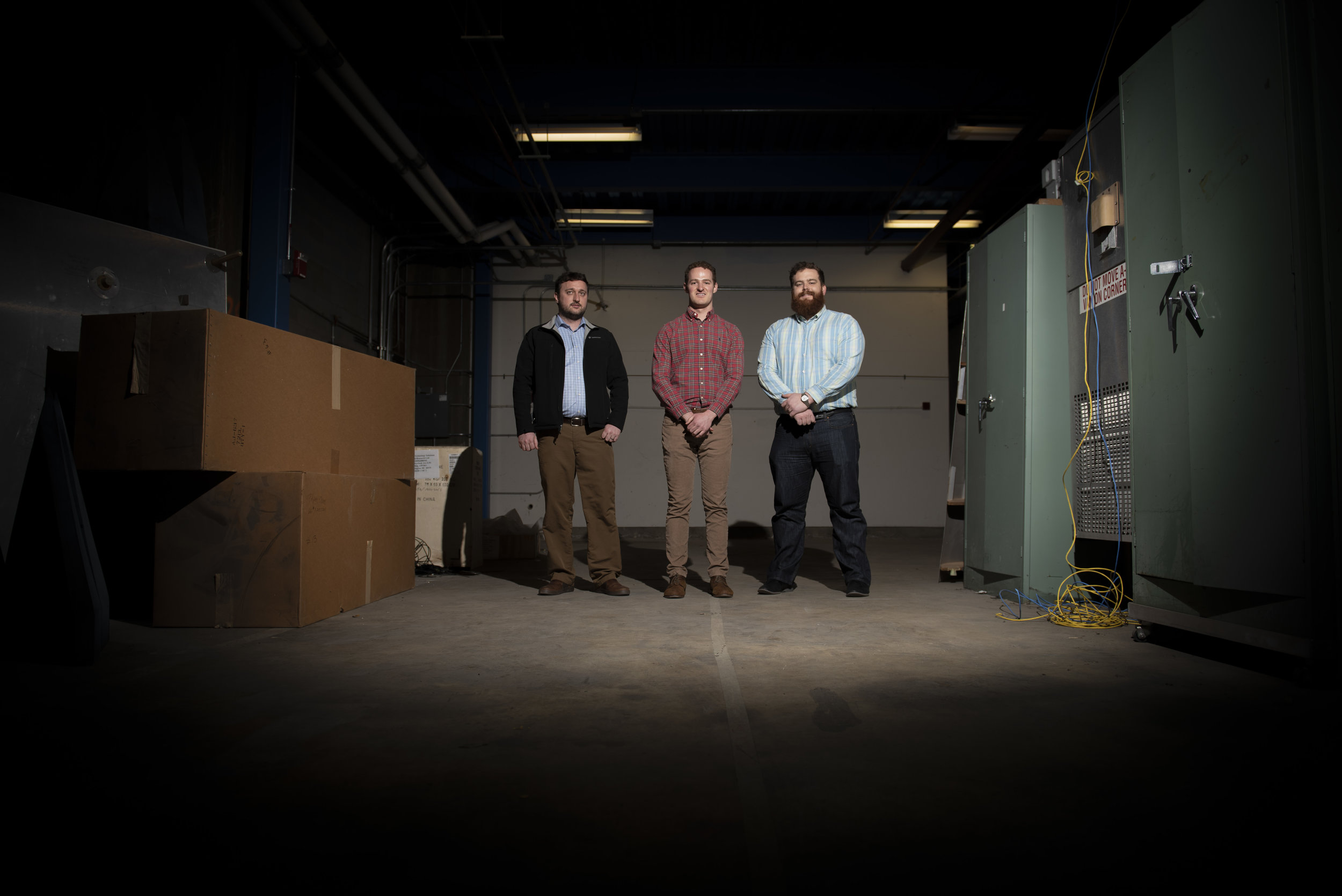 Mechanical engineers Jesse Maxwell (left), Evan Rogers (center) and Austin Phoenix (right) stand in the 4,000 square foot space that will soon be home to a new wind tunnel. (Photo by Jonathan Steffen)