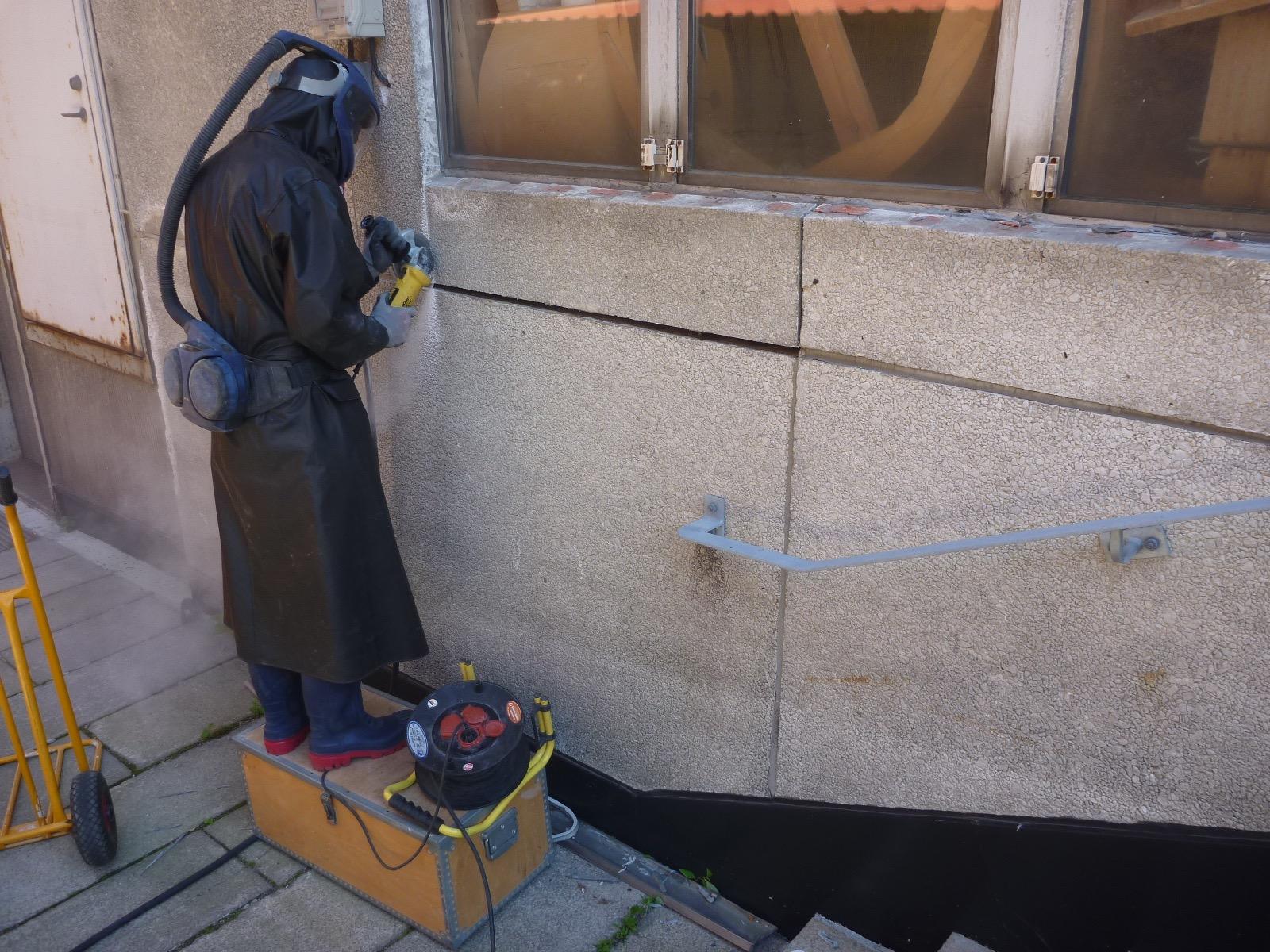 Nils skär ut en del av fasaden