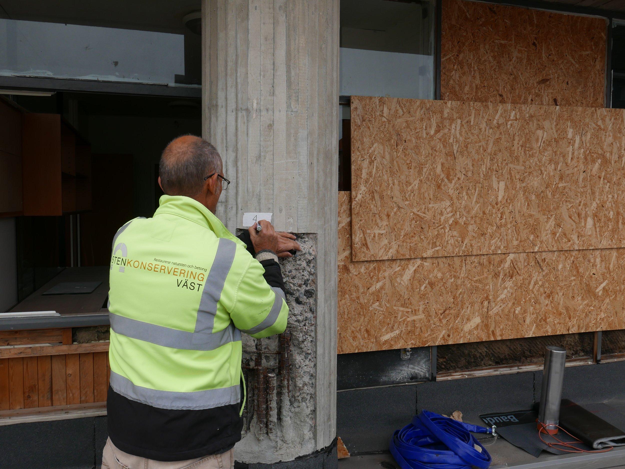 Nils markerar ut en av pelarna som ska åtgärdas