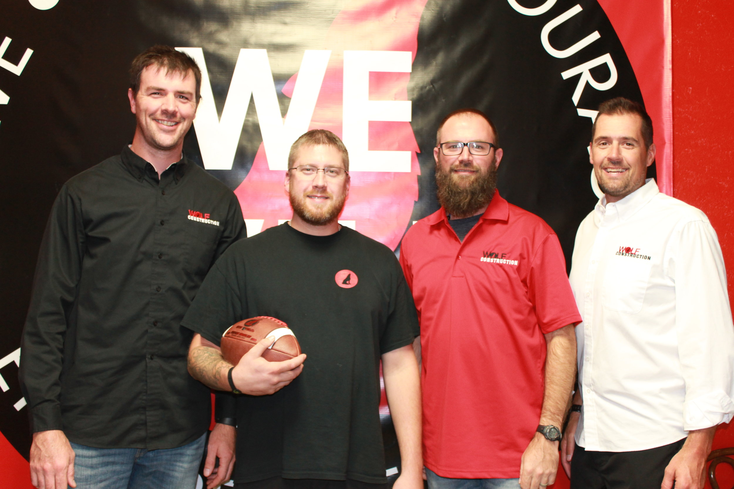 Stephen Huebshcen was presented the Wolf Construction Services, Inc. Game Ball in September 2018. A Foremen for the Trim Division, Stephen has taken on multiple large projects with confidence and shown quiet leadership both on and off the job site. A member of the Wolf Team since 2016, Stephen is a dedicated team member who is always working toward solutions.  Stephen and his family live in Pella. Pictured: R VanDis, S Huebschen, J VanDis, B Hoch