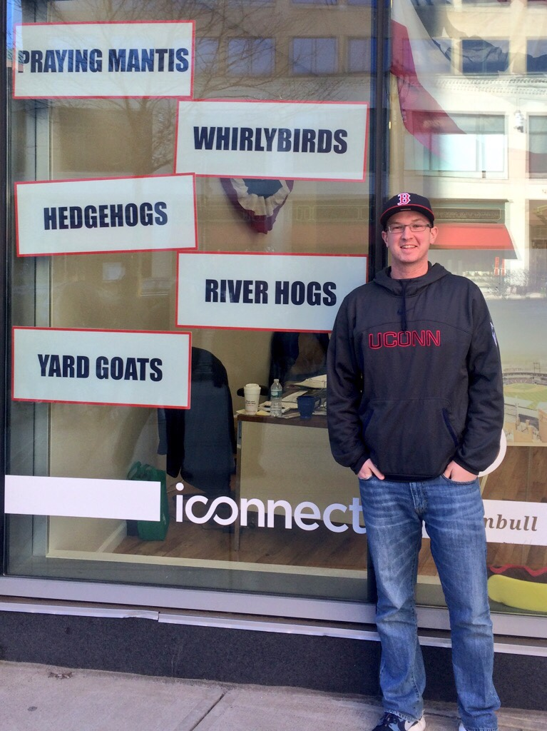 The author stands in front of the New Britain Rock Cats front office building during the team's re-branding process. The signs indicate new team names the franchise was considering. (Courtesy/Daniel Madigan)