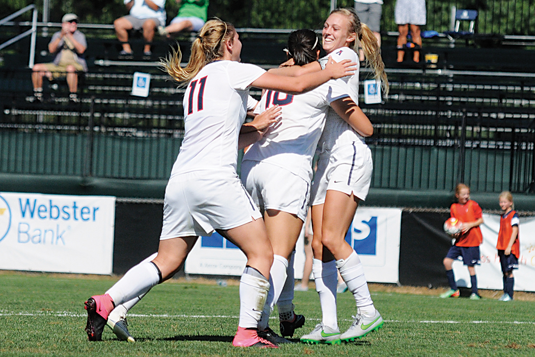 Members of the UConn women's soccer team celebrate with forward Rachel Hill (far right) after her late game winner against Harvard on Sunday, Sept. 6, 2015. The Huskies improved to 5-0 this season with the win over the Crimson. (Amar Batra/The Daily Campus)