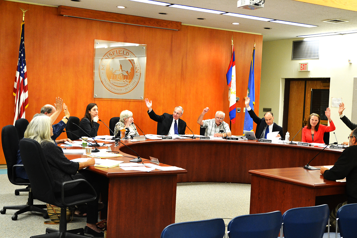 In this photo, members of the Mansfield Town Council raise their hands during a vote at a town council meeting in Mansfield, Connecticut on Monday, Sept. 28, 2015. (The Daily Campus)
