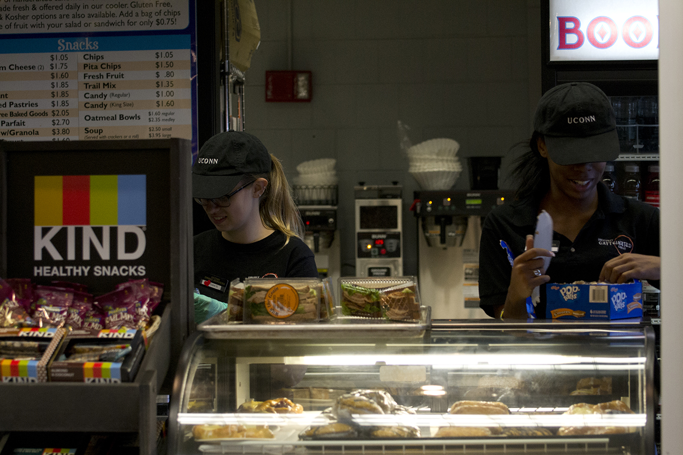 In this photo, two student employees are pictured at the Bookworms Café in UConn's Homer D. Babbidge Library.Almost six weeks into the semester, the cafés are experiencing the worst understaffing Dining Services has ever seen. (Rebecca Newman/The Daily Campus)