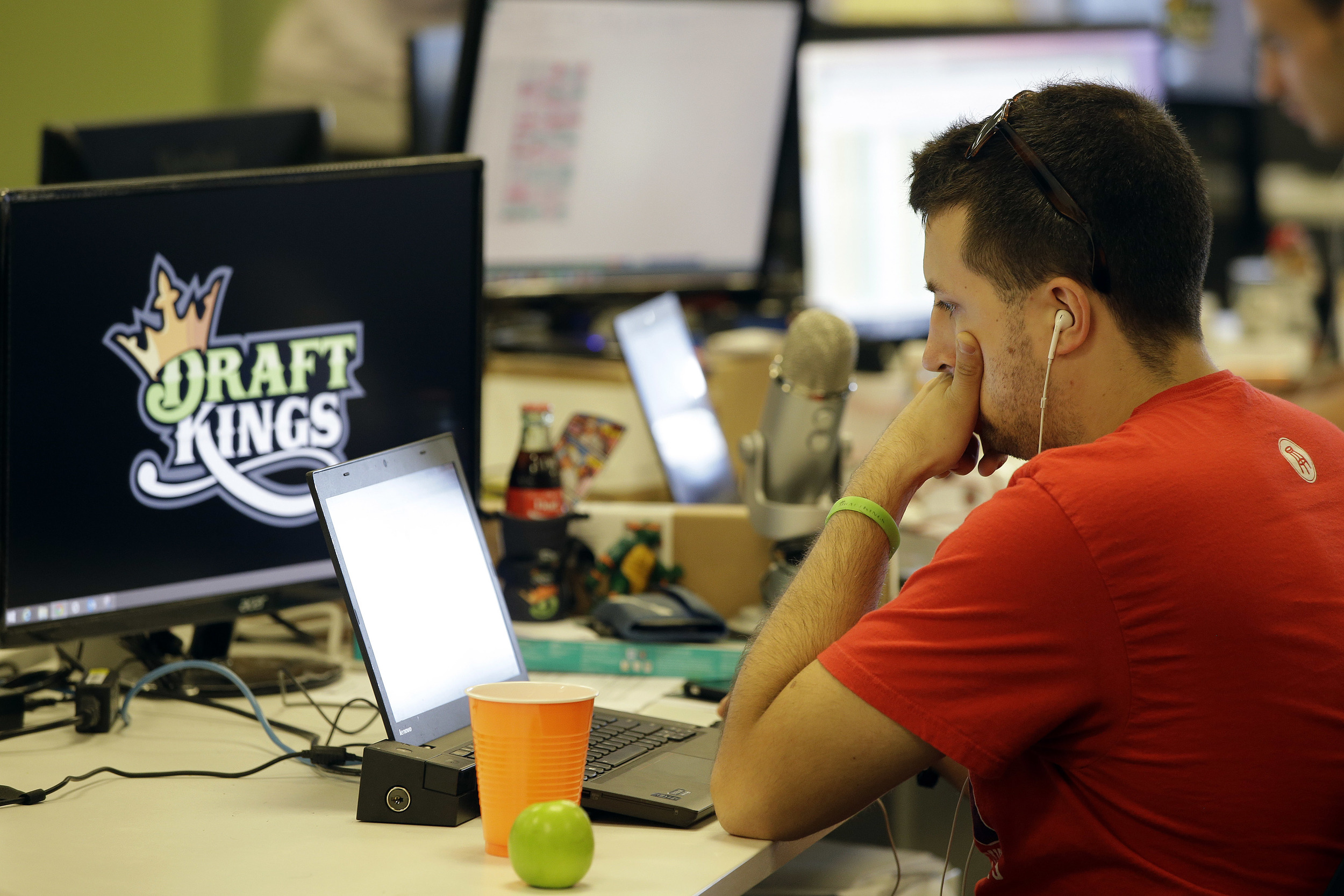 In this Sept. 9, 2015 file photo, Devlin D'Zmura, a tending news manager at DraftKings, a daily fantasy sports company, works on his laptop at the company's offices in Boston. Customers of the two biggest daily fantasy sports websites have filed at least four lawsuits against the sites in Oct. 2015, following cheating allegations and a probe into the largely-unregulated multi-billion dollar industry. (Stephan Savoia/AP)