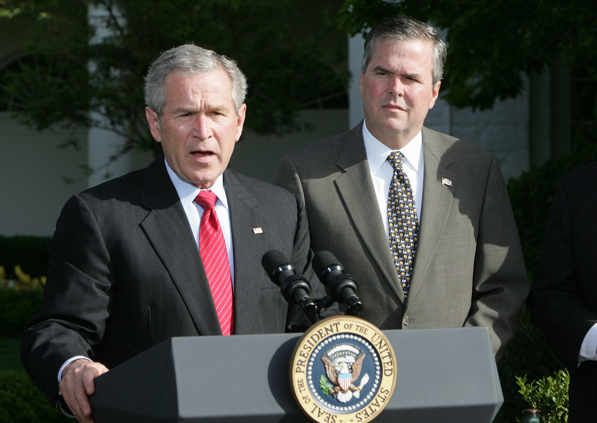 In this April 19, 2006 file photo, President George W. Bush, accompanied by his brother, then-Fla. Gov. Jeb Bush, speaks on the South Lawn at the White House in Washington. (Ron Edmonds, File/AP)