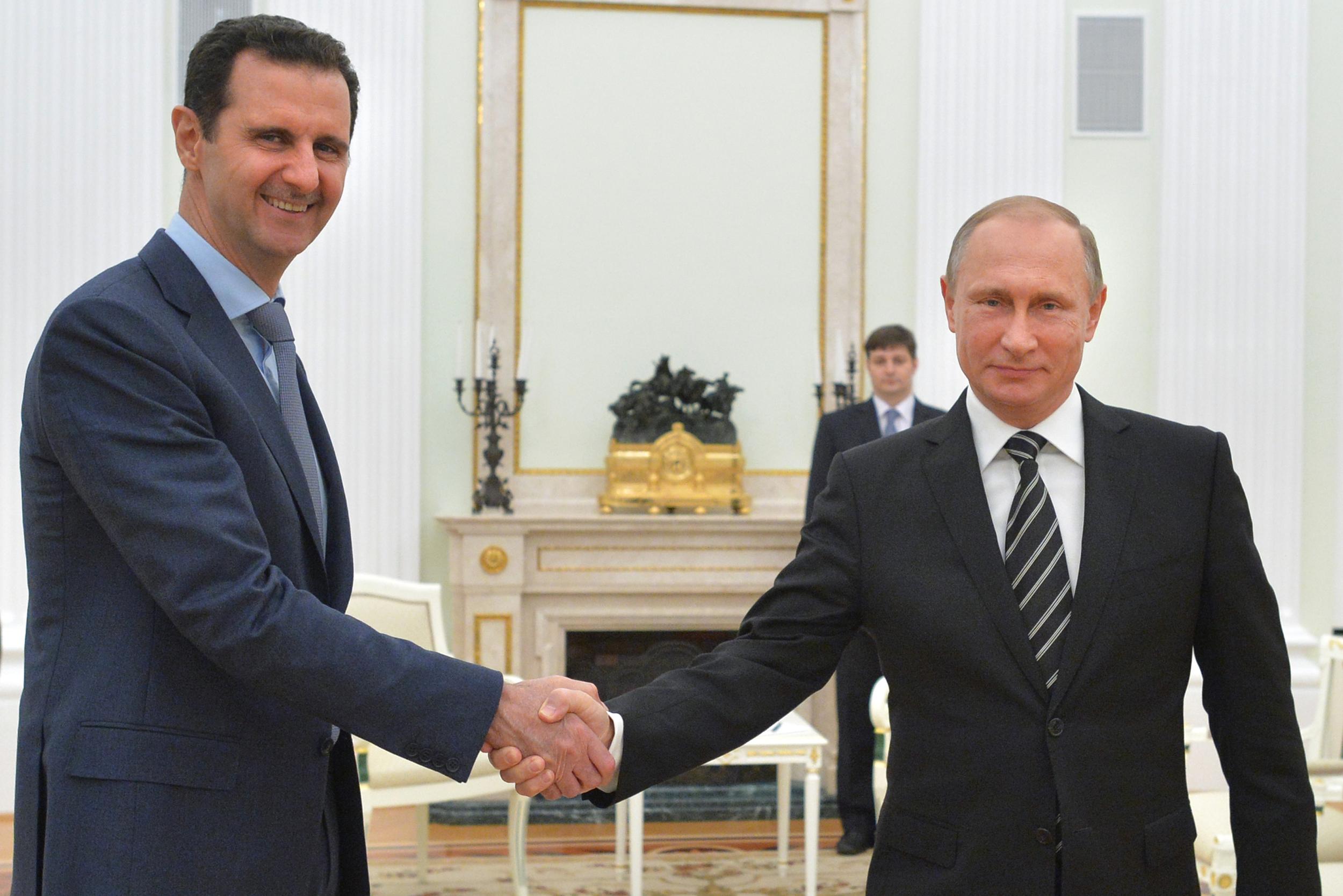 In this photo taken on Tuesday, Oct. 20, 2015, Russian President Vladimir Putin, right, shakes hand with Syria's President Bashar al-Assad in the Kremlin in Moscow, Russia. (Alexei Druzhinin, RIA-Novosti, Kremlin Pool Photo via AP)