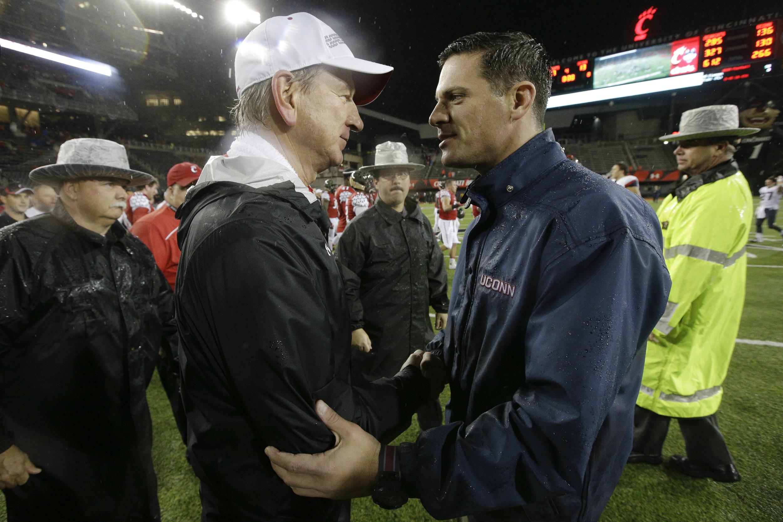 Cincinnati head coach Tommy Tuberville, left, shakes hands with Connecticut head coach Bob Diaco after an NCAA college football game, Saturday, Oct. 24, 2015, in Cincinnati. Cincinnati won 37-13. (John Minchillo/AP)