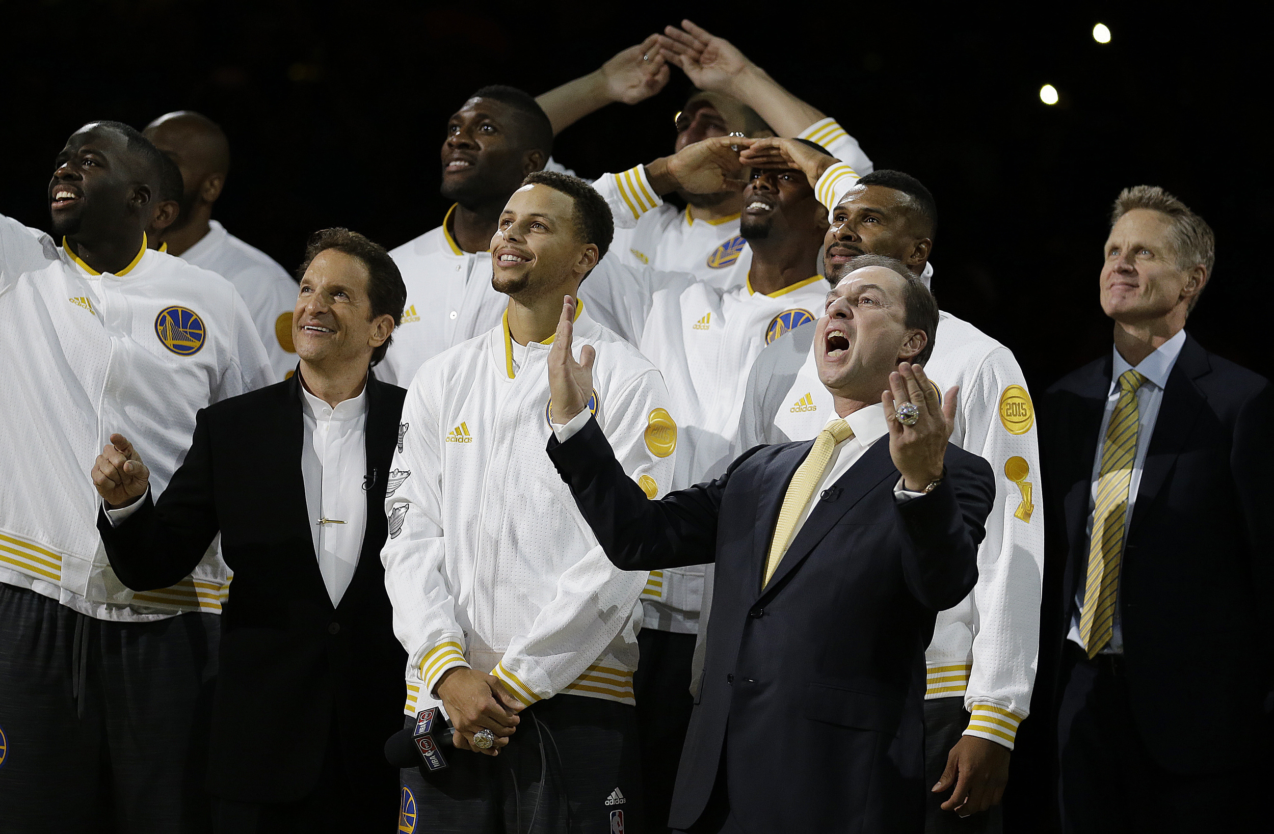 Golden State Warriors co-owner Joe Lacob, front right, reacts beside Stephen Curry and co-owner Peter Guber, second from left, as the Warriors championship banner is revealed during an awards ceremony to recognize the Warriors' NBA championship prior to a basketball game against the New Orleans Pelicans, Tuesday, Oct. 27, 2015, in Oakland, Calif. At right is Warriors coach Steve Kerr. (Ben Margot/AP)