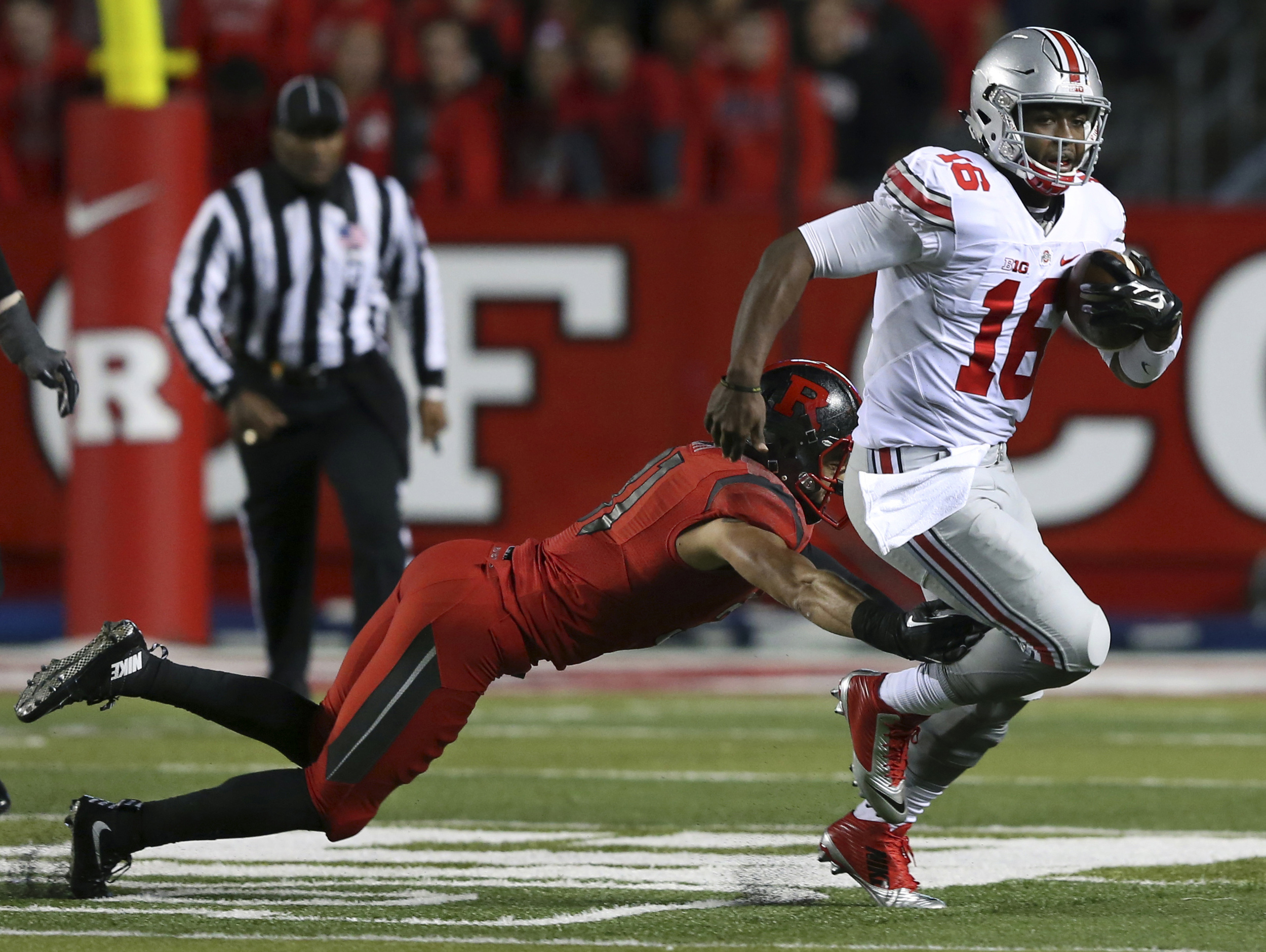 Ohio State quarterback J.T.Barrett (16) breaks a tackle by Rutgers defensive back Anthony Cioffi (31) during the first half of an NCAA college football game Saturday, Oct. 24, 2015, in Piscataway, N.J. (AP).