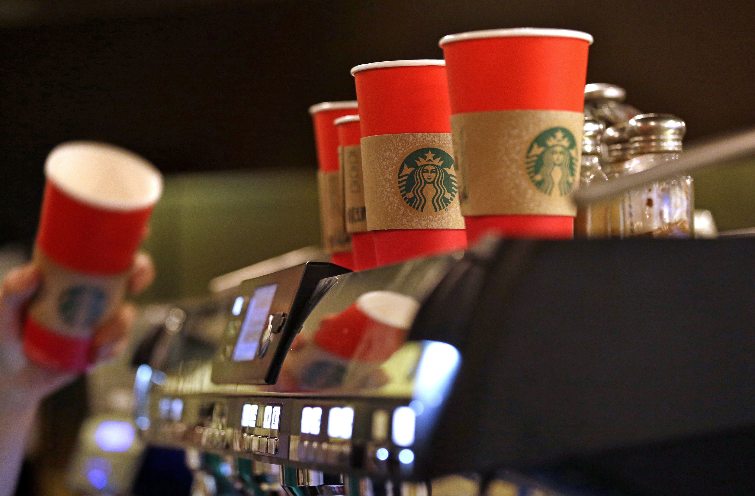 A barista reaches for a red paper cup as more, with cardboard liners already attached, line the top of an espresso machine at a Starbucks coffee shop in the Pike Place Market, Tuesday, Nov. 10, 2015, in Seattle. It's as red as Santa's suit, a poinsettia blossom or a loud Christmas sweater. Yet Starbucks' minimalist new holiday coffee cup has set off complaints that the chain is making war on Christmas. (Elaine Thompson/AP)