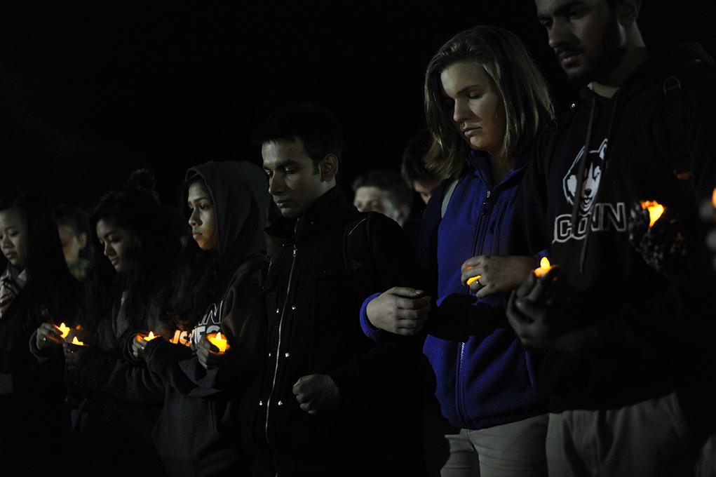 Students hold candles at the vigil on Fairfield Way. (Jason Jiang/Daily Campus)