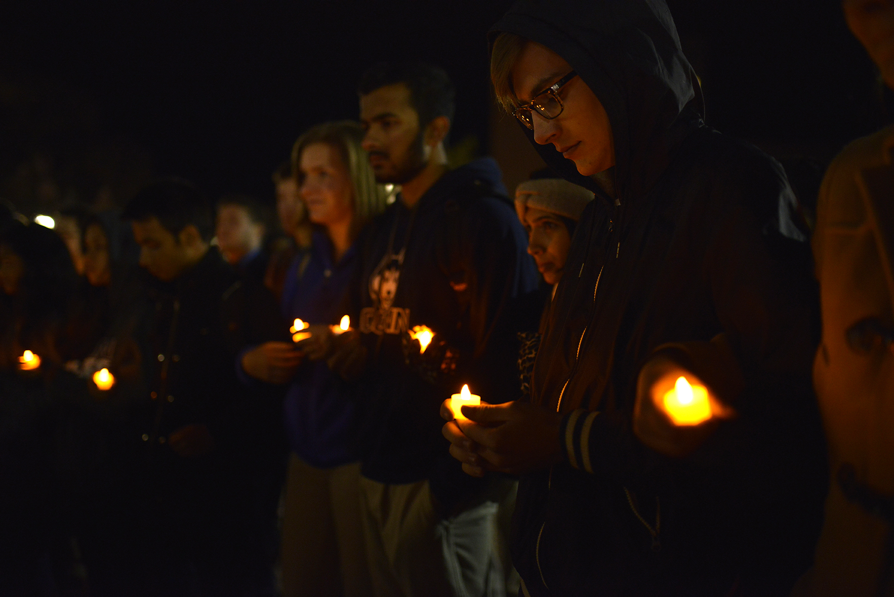 """Students hold candles as part of a vigil on Fairfield Way Wed., Nov. 18 to honor victims of Islamophobia. The vigil was held by Asian American Cultural Center (AsAAC) as part of a series named """"Salaam."""" (Jason Jiang/Daily Campus)"""