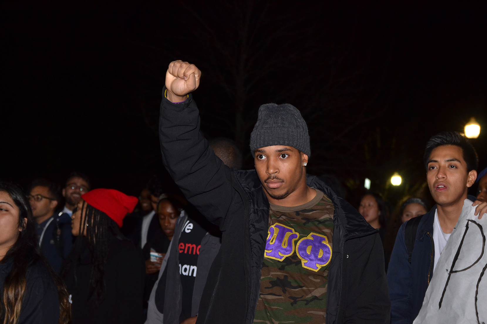 "UConn student Josh Marriner, also a running back on the UConn football team, holds up a fist while walking in the ""March for Justice, Empowerment and Solidarity"" on Fairfield Way in Storrs, Connecticut on Thursday, Nov. 19, 2015. (Amar Batra/The Daily Campus)"