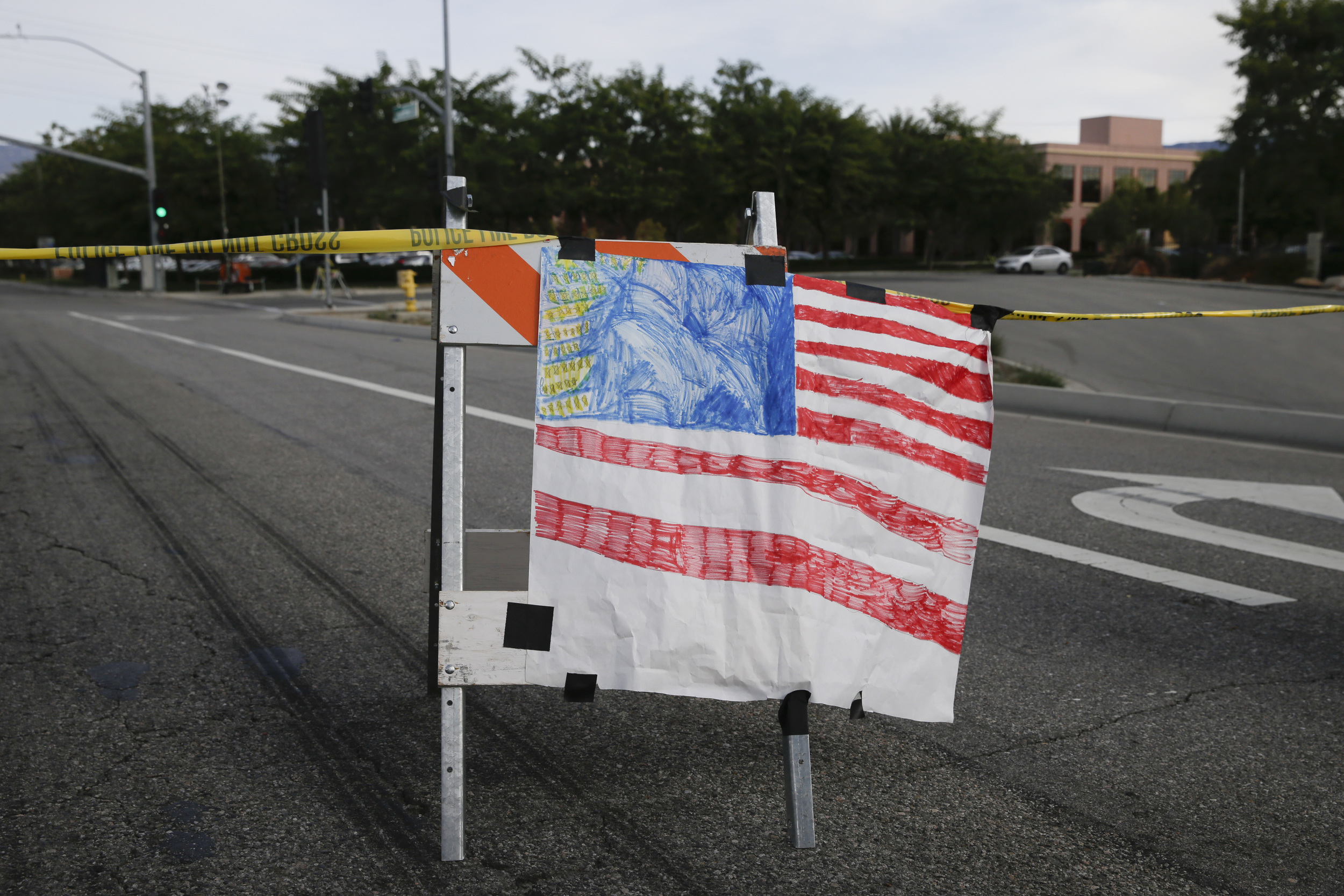 A hand-painted American flag is seen near the building, top right, where Wednesday's shooting rampage took place, at the Inland Regional Center, Sunday, Dec. 6, 2015, in San Bernardino, Calif. The FBI said it's investigating the massacre in San Bernardino, California, that killed 14 and injured 21 as a terrorist attack. (Jae C. Hong/AP)