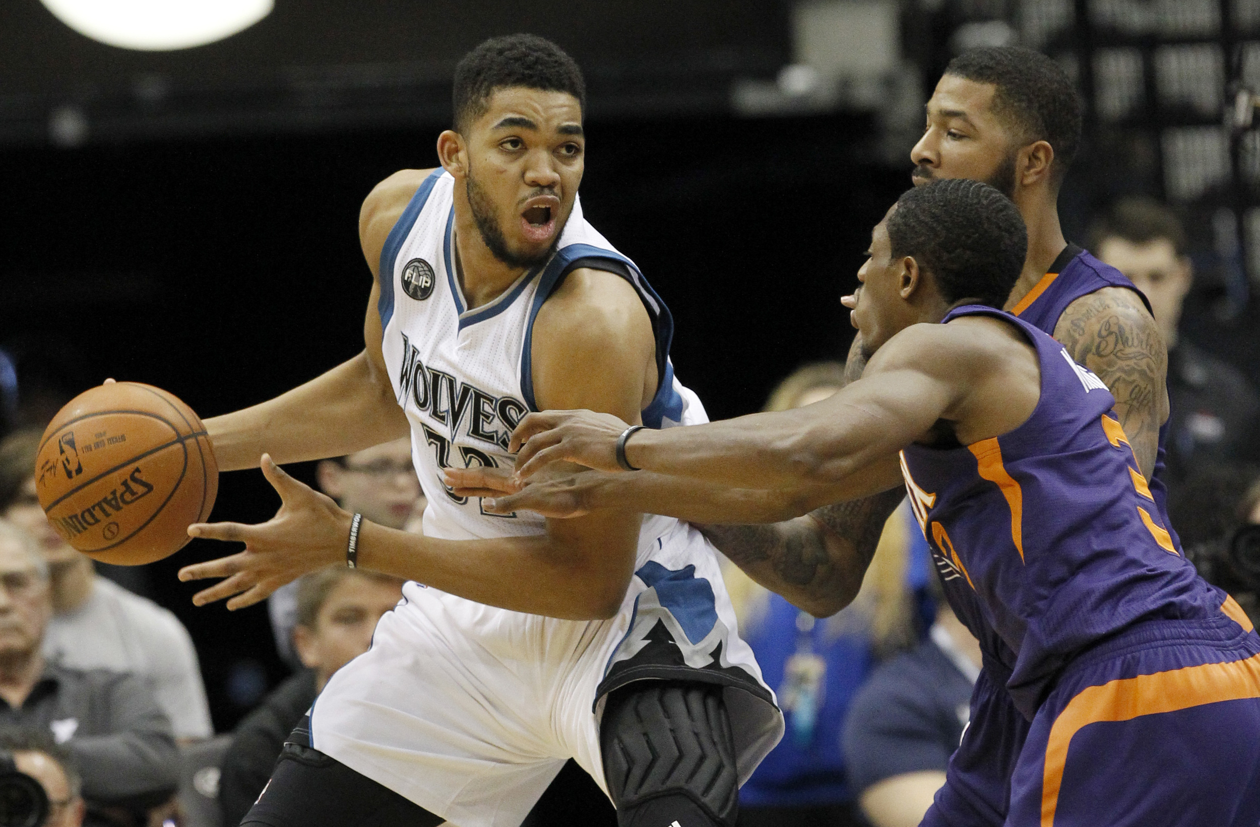Minnesota Timberwolves center Karl-Anthony Towns, left, looks to pass to a teammate under pressure from Phoenix Suns forward Markieff Morris, right rear, and Suns guard Brandon Knight, right front, during the second half of an NBA basketball game in Minneapolis, Sunday, Jan. 17, 2016. (Ann Heisenfelt/AP)