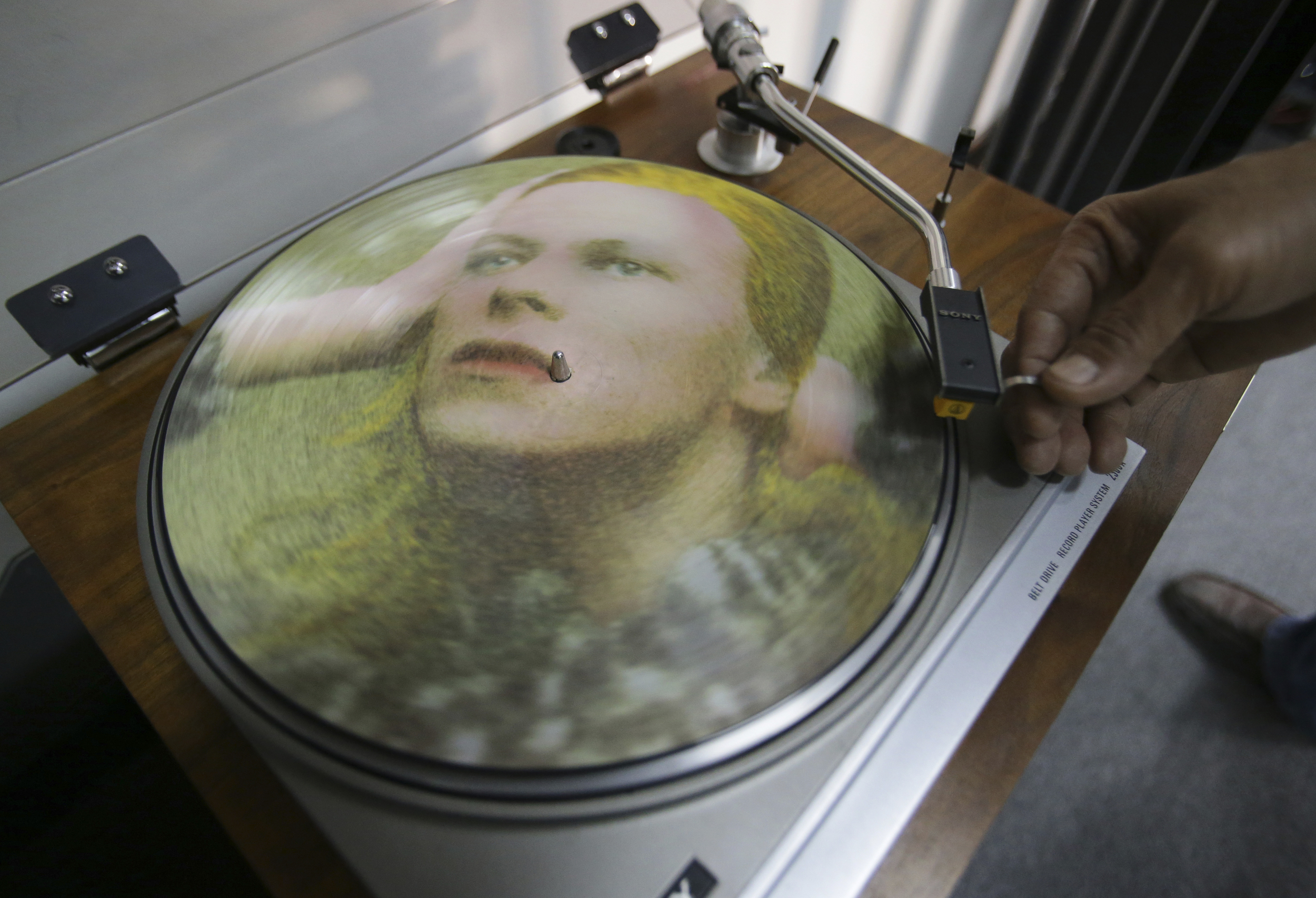 In this Tuesday, Jan. 12, 2016 photo, Rene Rivo, a Filipino David Bowie fan, plays a picture disc of Bowie's Hunky Dory on a turntable at his shop in suburban Paranaque, south of Manila, Philippines. (Aaron Favila, File/AP)