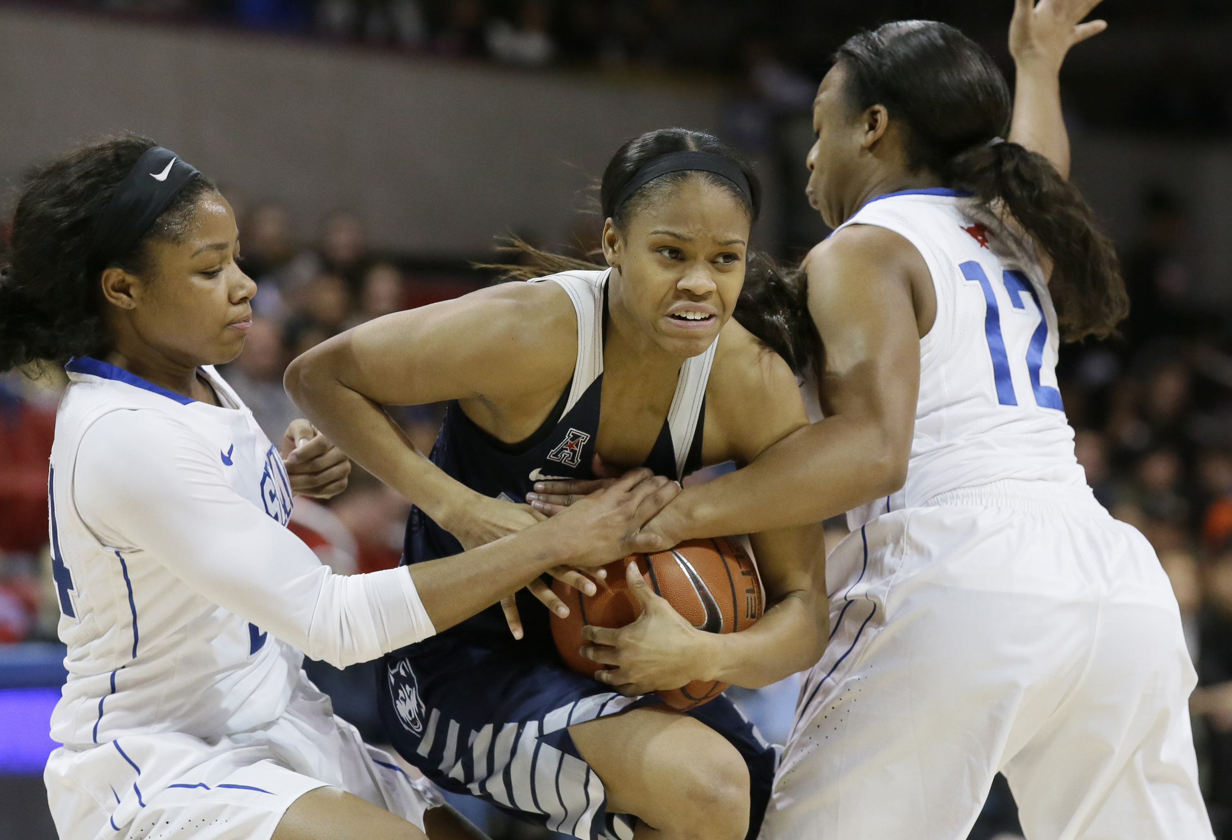 Connecticut guard Moriah Jefferson, center, drives between SMU guards Morgan Bolton (12) and Kamray Mickens (24) during the second half of an NCAA college basketball game Saturday, Jan. 23, 2016, in Dallas. UConn won 90-37. (LM Otero/AP)