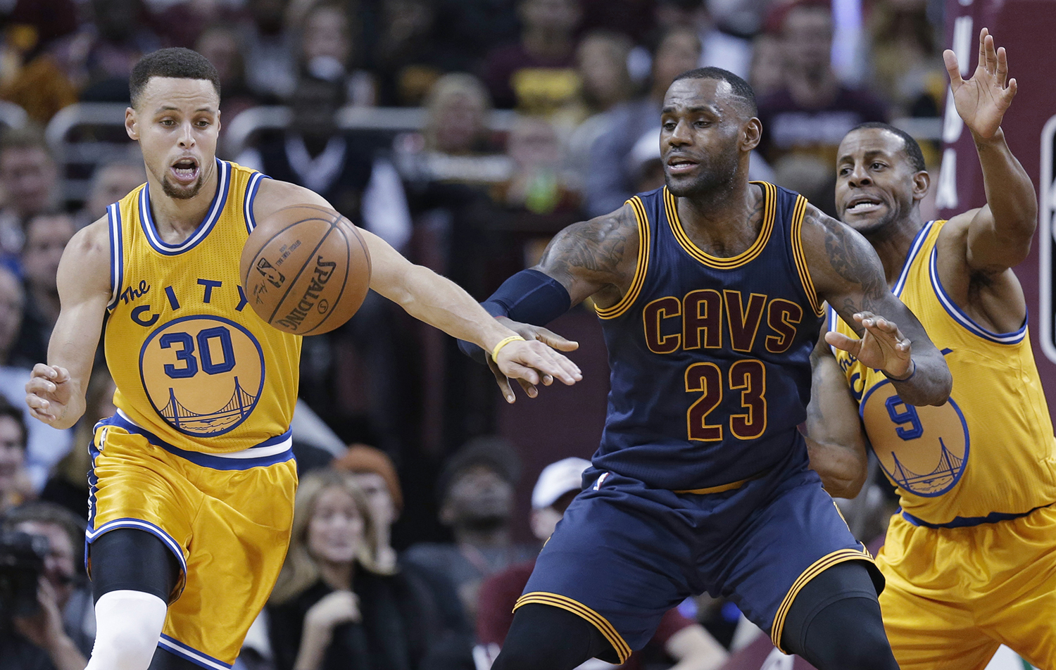 Golden State  Warriors ' Stephen Curry (30) knocks the ball loose from Cleveland  Cavaliers ' LeBron James (23) in the first half of an NBA basketball game, Monday, Jan. 18, 2016, in Cleveland. Andre Iguodala (9) is at right. (AP Photo/Tony Dejak)