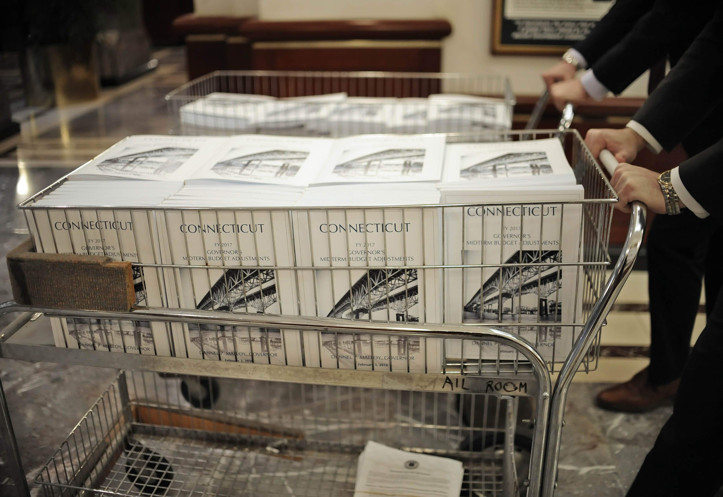 Legislative aides push copies of Connecticut's budget plan through the Legislative Office Building, Wednesday, Feb. 3, 2016, in Hartford, Conn. Connecticut Gov. Dannel P. Malloy is proposing to reduce spending for next fiscal year's budget by $569 million. (AP)