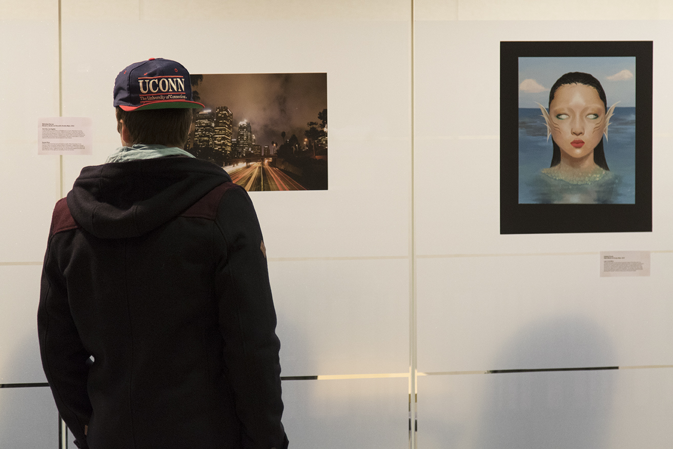 A student views artwork during a student art exhibition hosted by the Center for Career Development on the second floor of the Wilbur Cross Building on Wednesday, Feb. 10, 2016. (Jackson Mitchell/The Daily Campus)