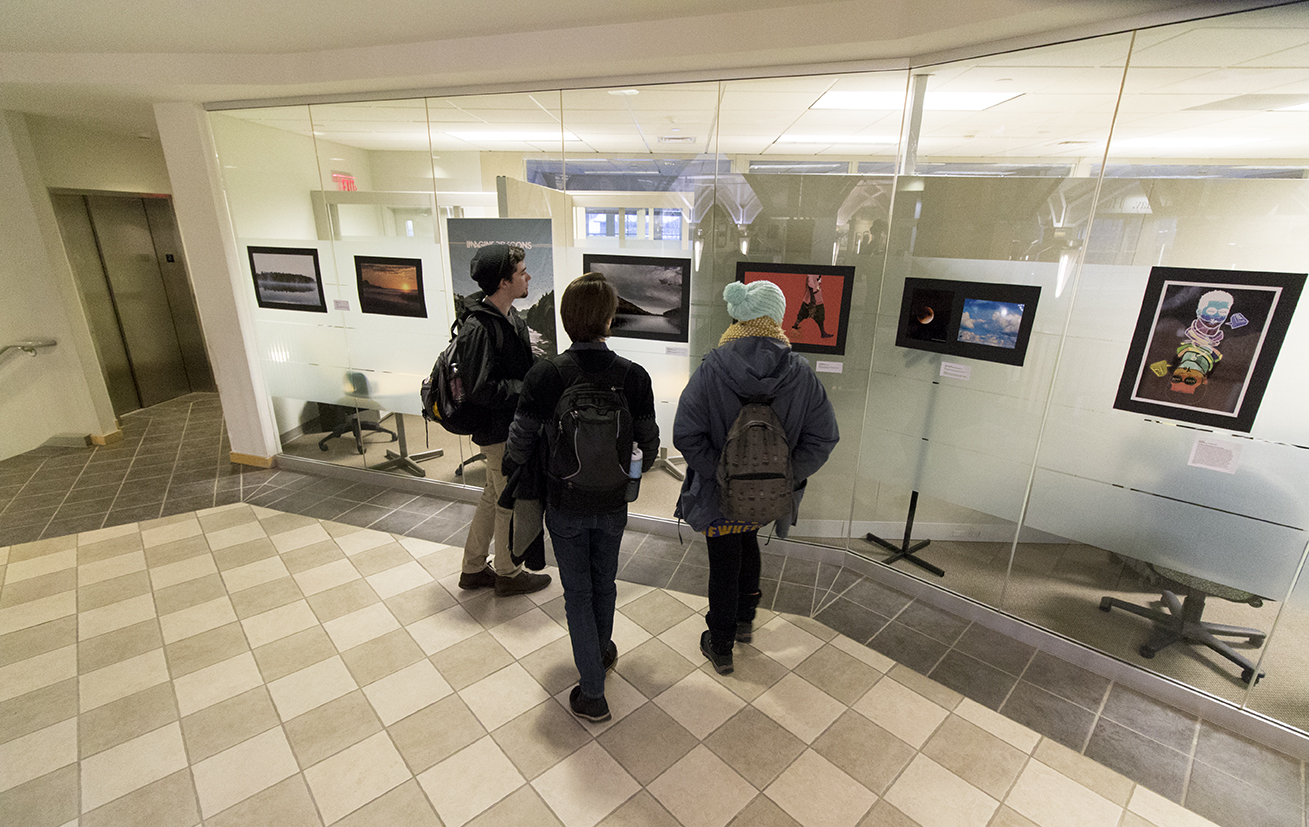 Students view artwork during a student art exhibition hosted by the Center for Career Development on the second floor of the Wilbur Cross Building on Wednesday, Feb. 10, 2016.(Jackson Mitchell/The Daily Campus)