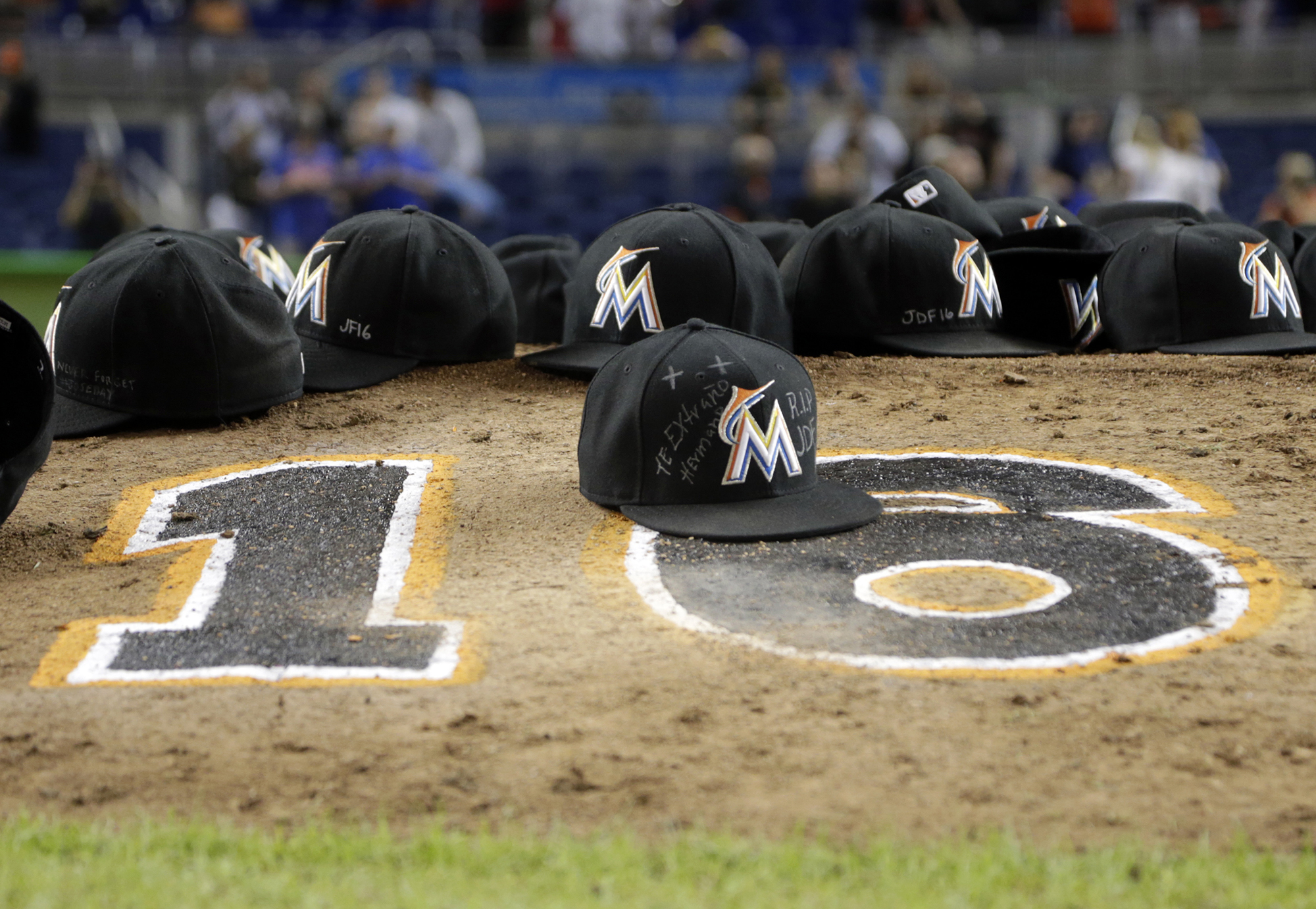 Miami Marlins ball caps left by the players sit on the pitching mound with the number 16 in honor of pitcher Jose Fernandez after a baseball game against the New York Mets, Monday, Sept. 26, 2016, in Miami. The Marlins defeated the Mets 7-3. (AP Photo/Lynne Sladky)