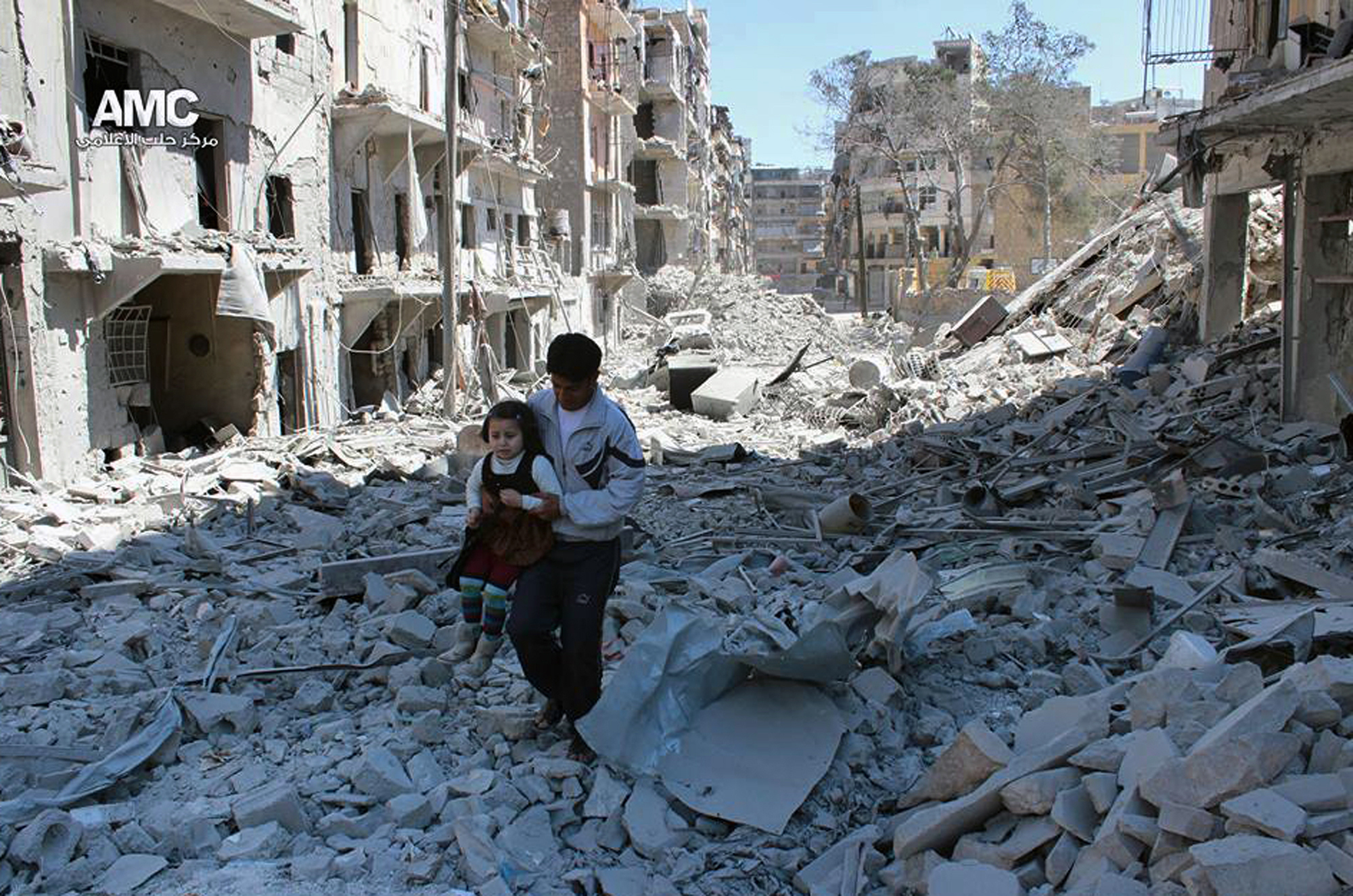 In This April 21, 2014, file photo, provided by the anti-government activist group Aleppo Media Center (AMC), which has been authenticated based on its contents and other AP reporting, shows a Syrian man holding a girl as he stands on the rubble of houses that were destroyed by Syrian government forces air strikes in Aleppo,Syria. (AP Photo/Aleppo Media Center AMC, File)